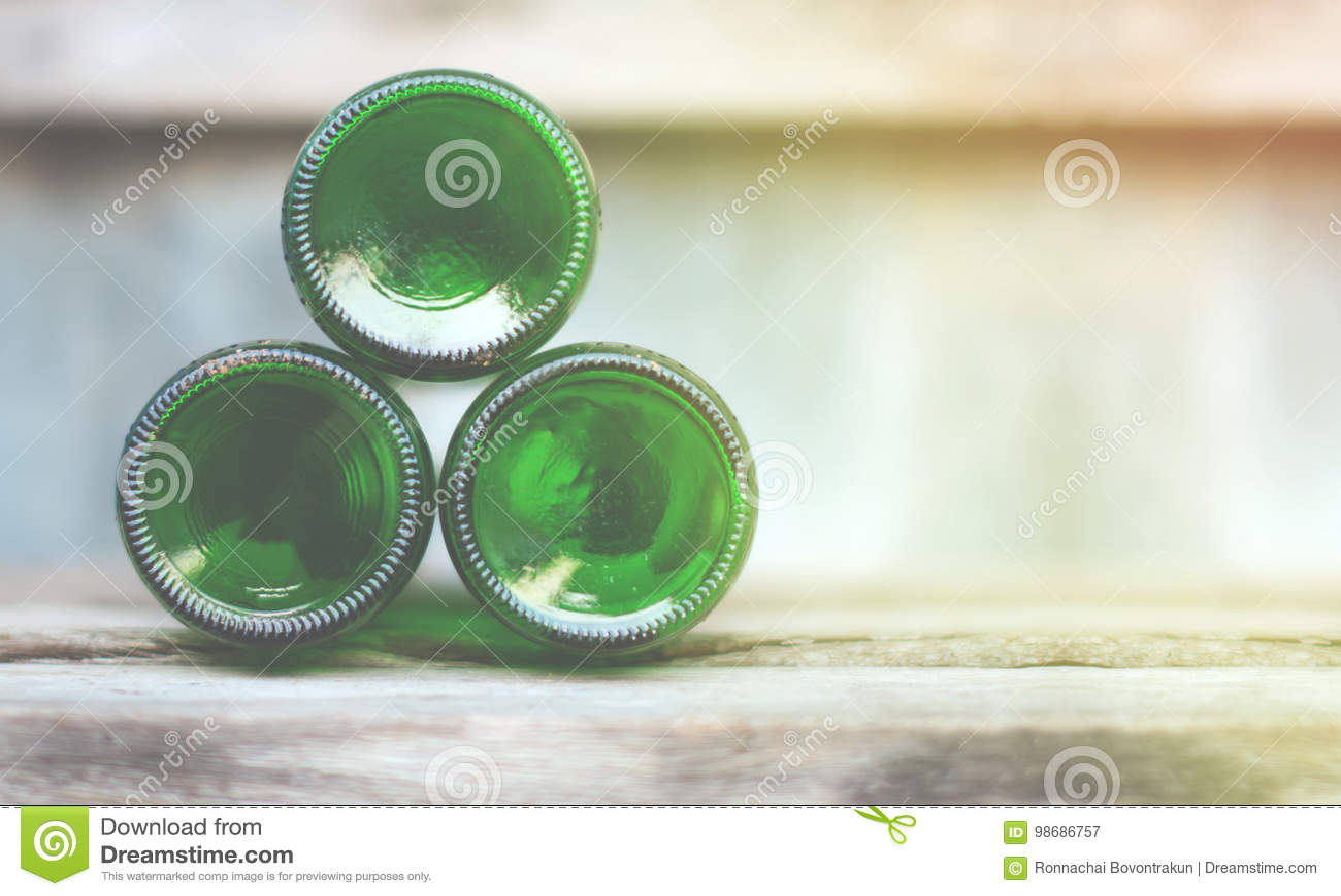 3 стеклянных бутылки, зеленые дн лежат вперед на деревянном