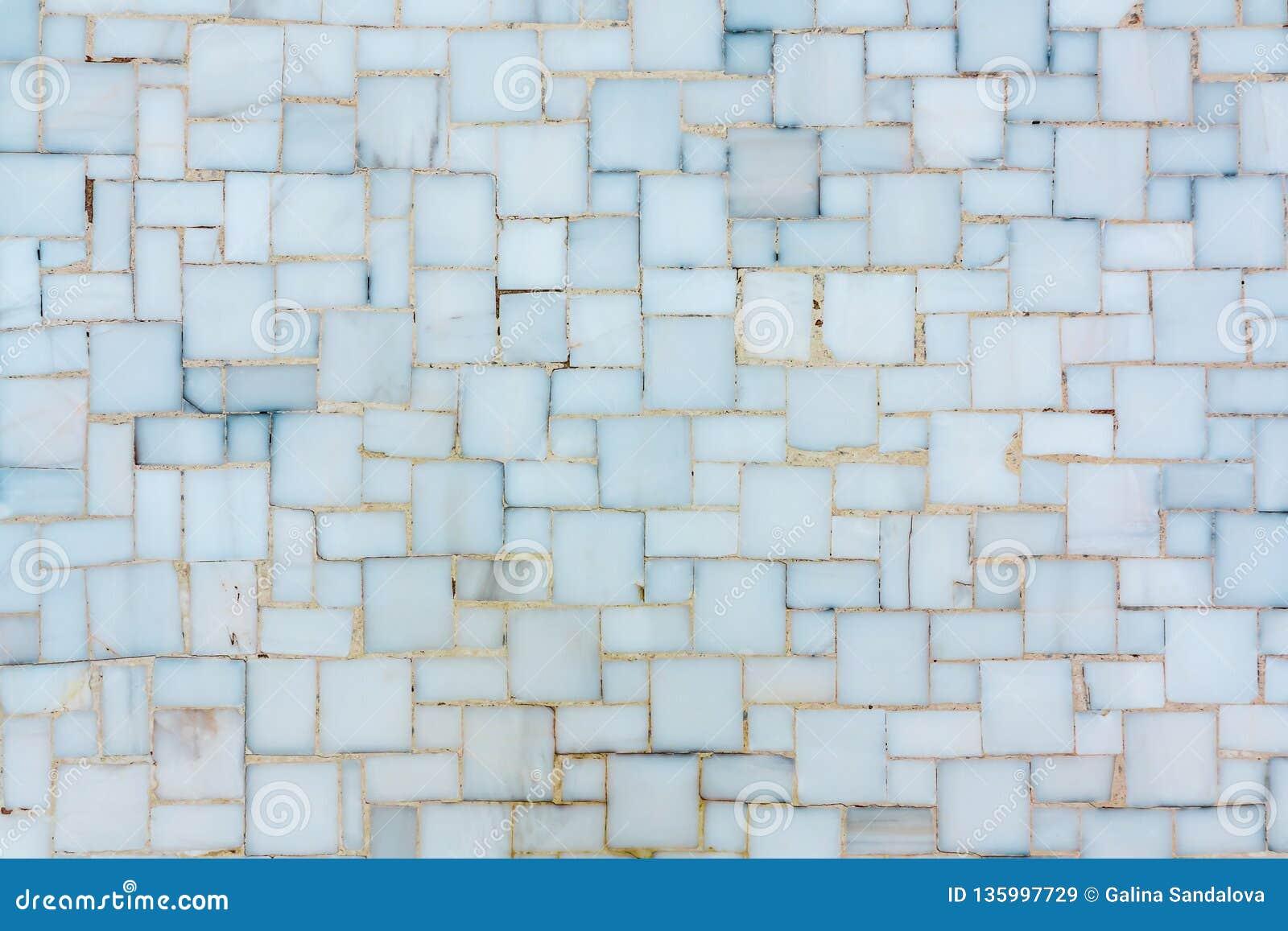 Стена выровнянная с небольшими яркими керамическими или мраморными плитками, текстурой