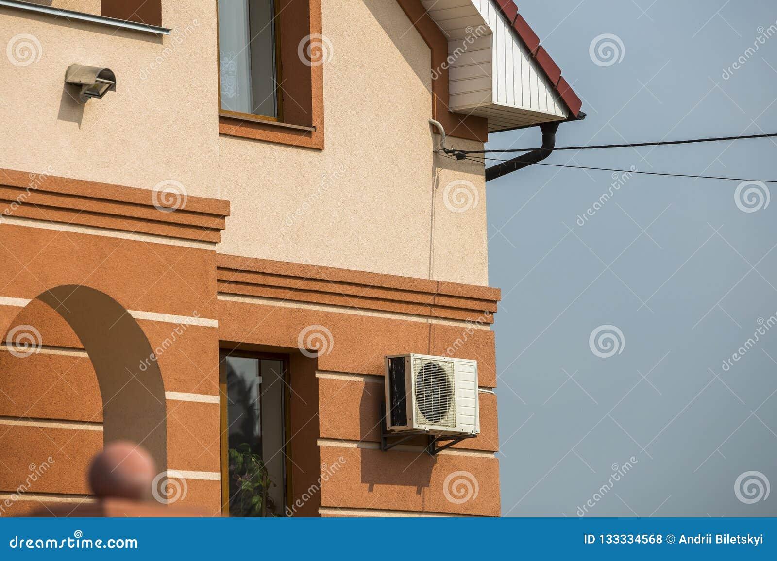 Стена штукатурки детали конца-вверх передняя большого современного дорогого жилого коттеджа семьи с кондиционером на предпосылке