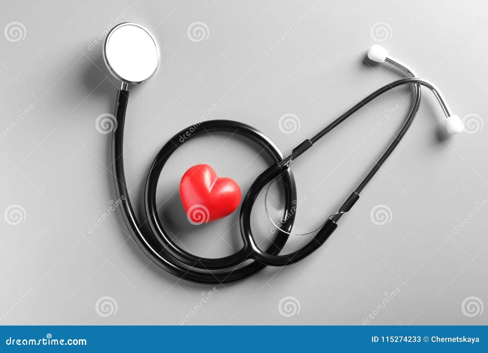 Стетоскоп и малое красное сердце на серой предпосылке