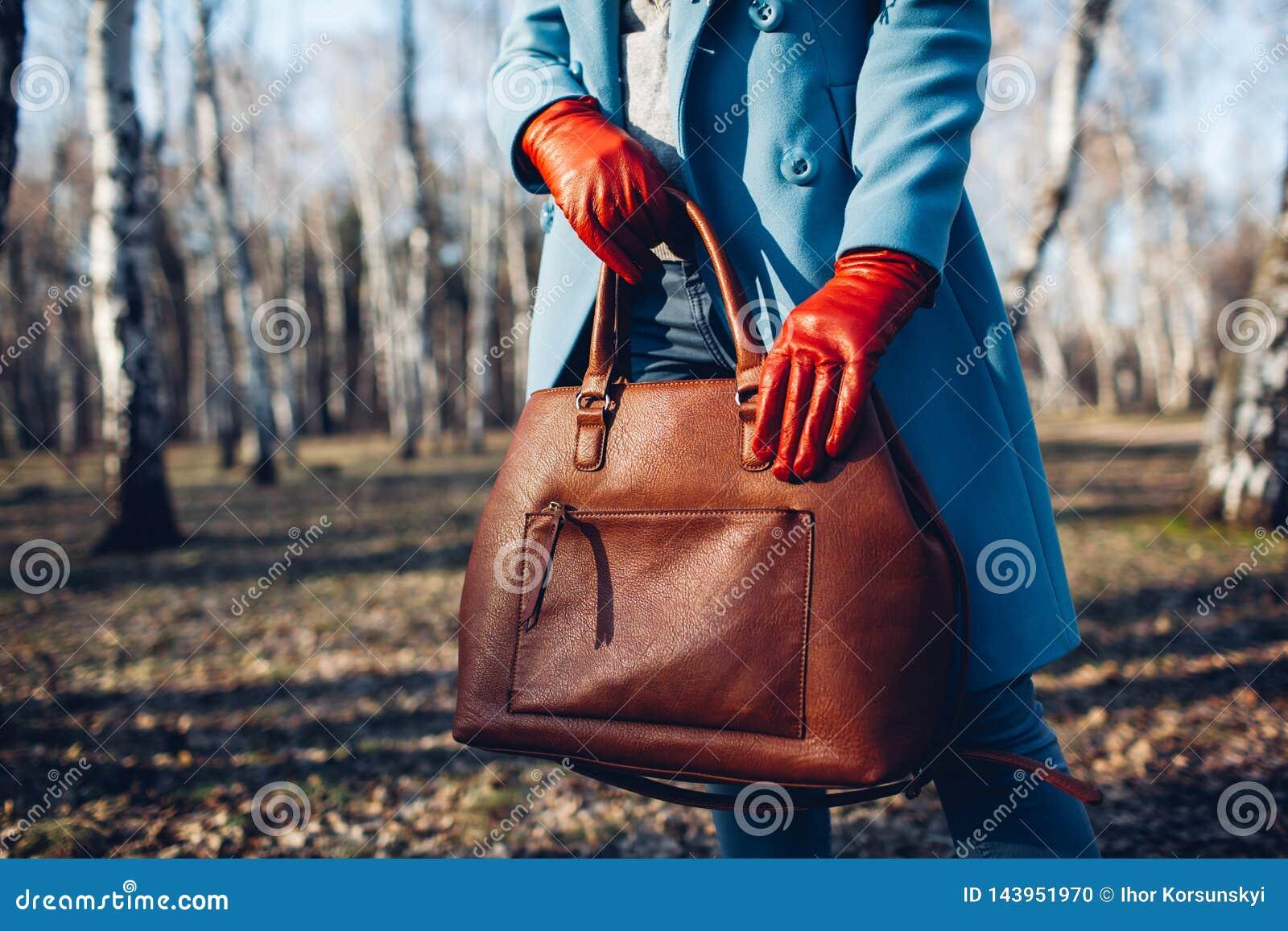 : Стильная модная женщина нося яркое платье держа коричневую сумку сумки