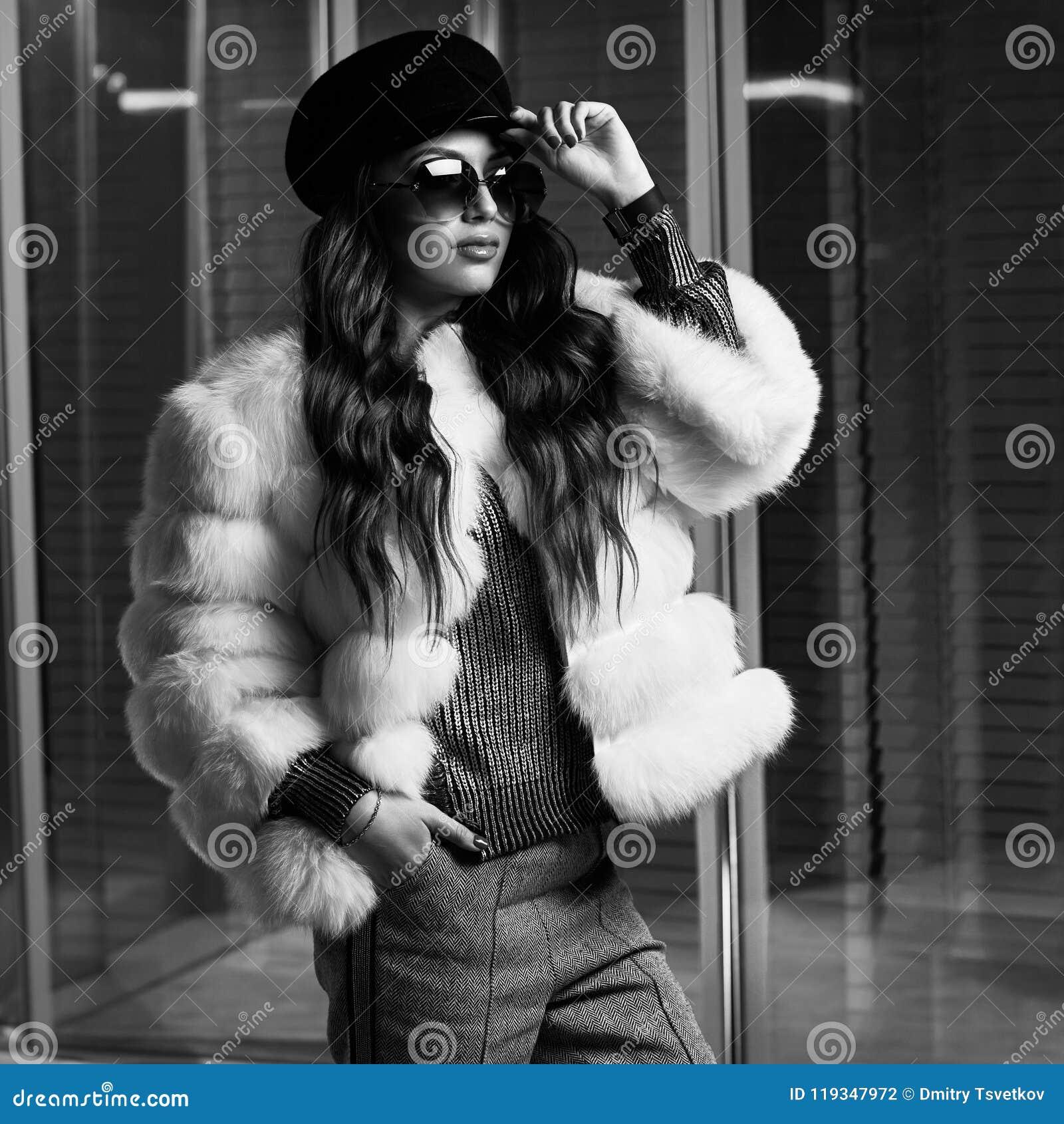 Стильная молодая женщина в белой меховой шыбе и круглых солнечных очках