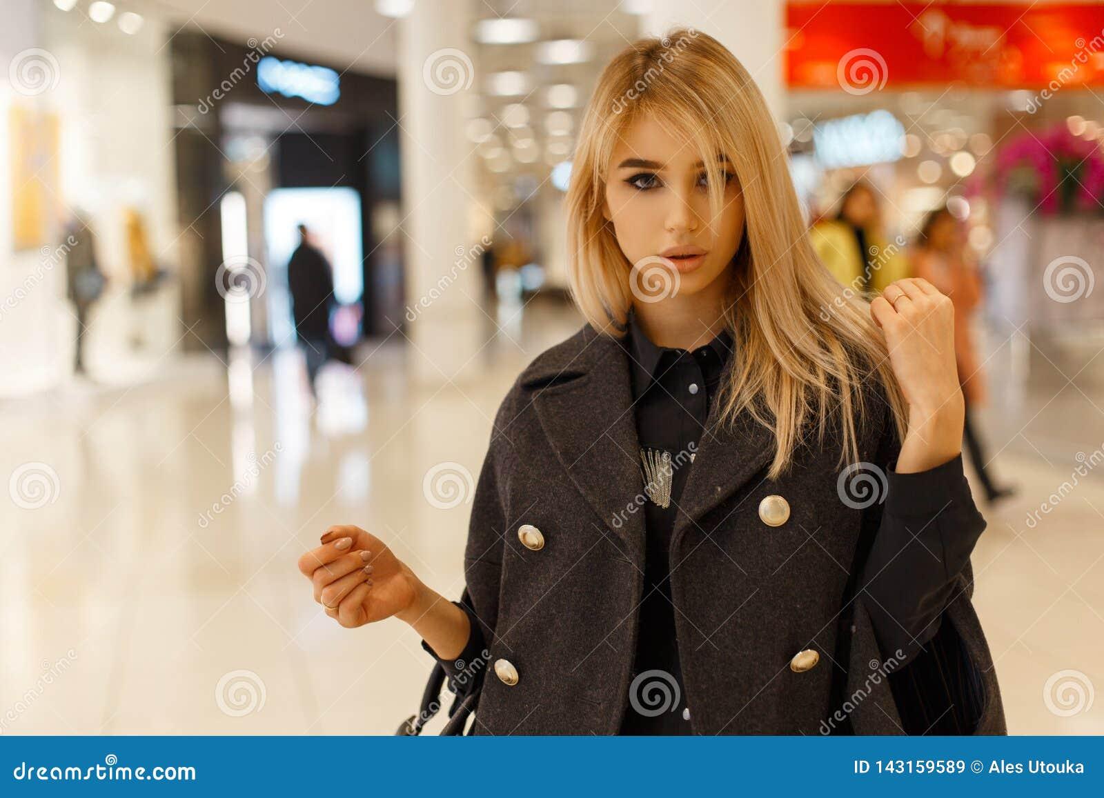 Стильная сексуальная молодая белокурая женщина с серыми глазами в стильном сером пальто в черной ультрамодной рубашке с кожаной ч