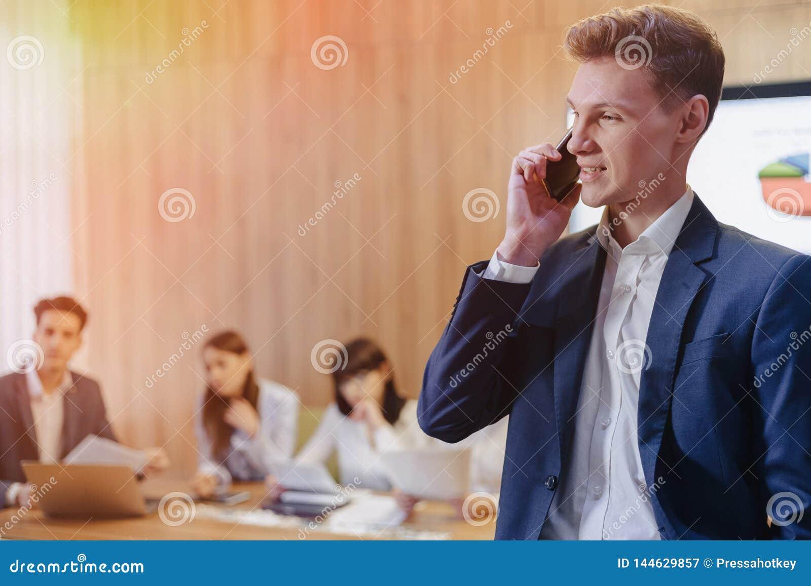 Стильный молодой бизнесмен нося куртку и рубашку на предпосылке работ