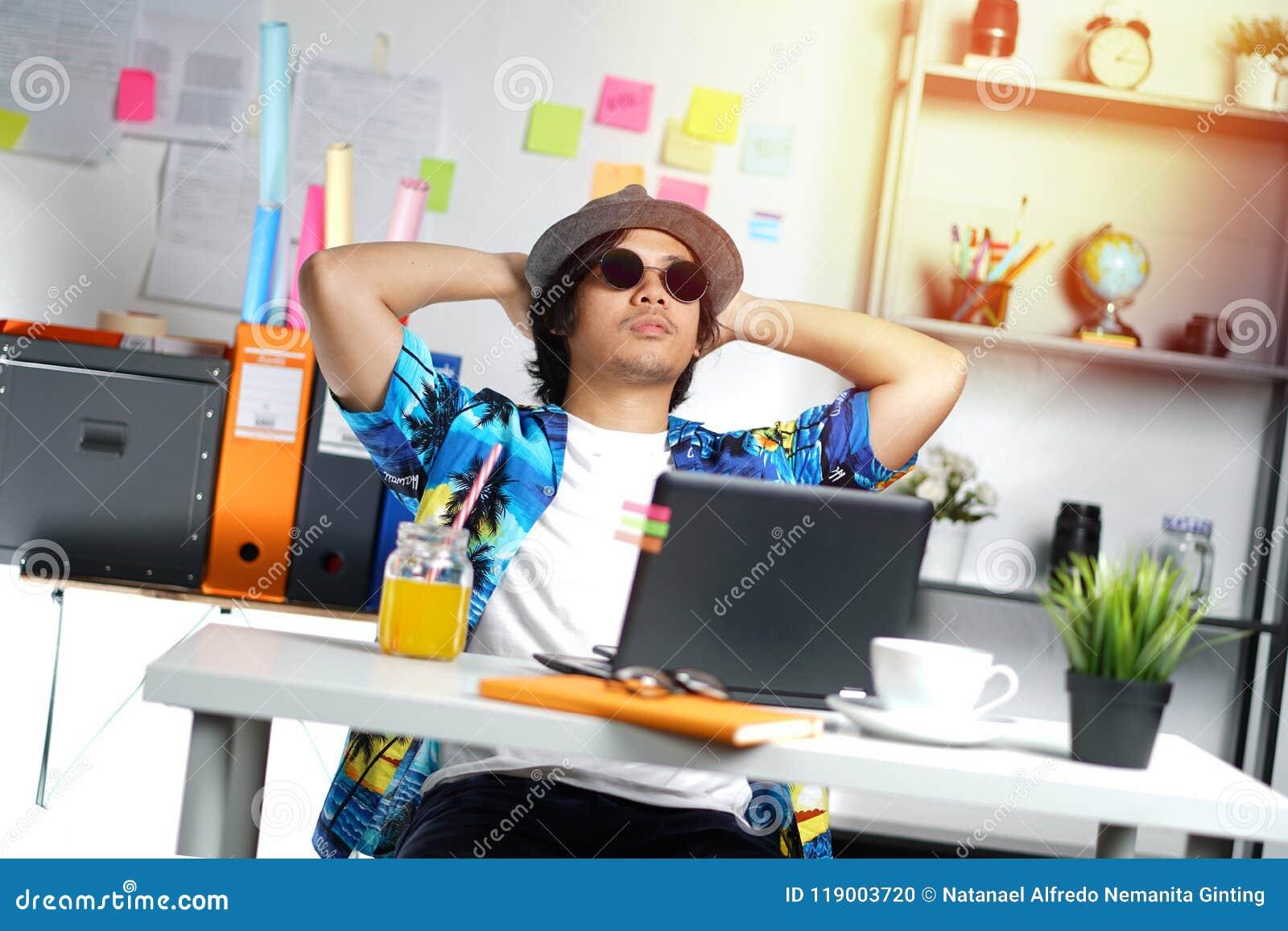 Стильный молодой профессионал наслаждаясь его праздником пока работающ дальше