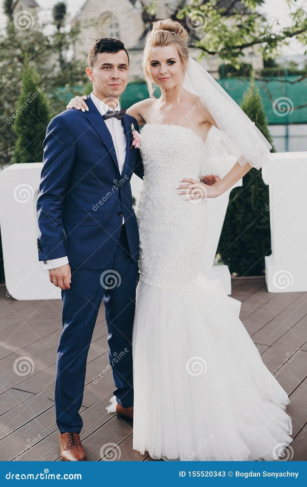 Стильный счастливый жених и невеста представляя на большом слове любов в выравнивать свет на приеме по случаю бракосочетания outd