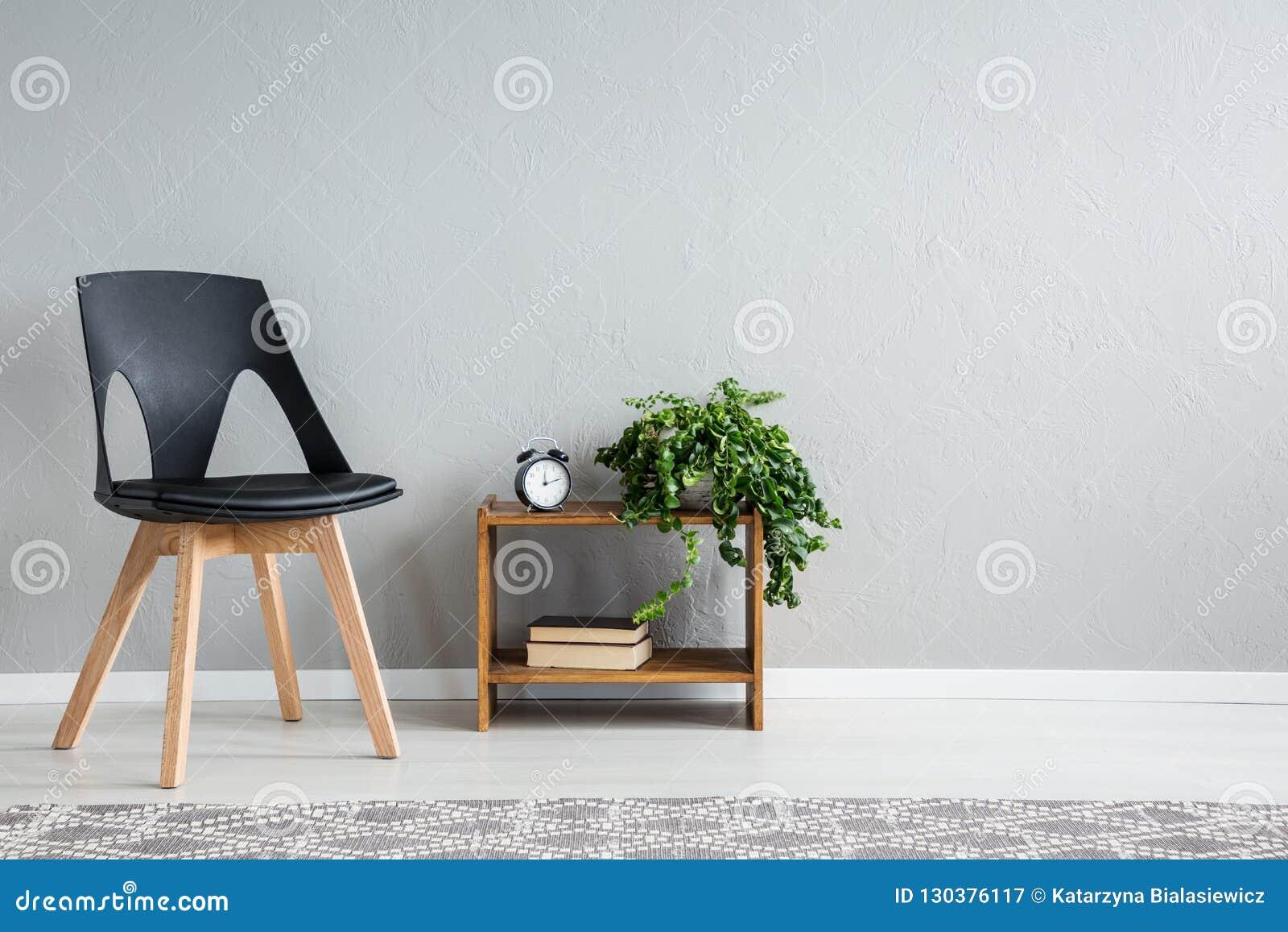 Стильный черный стул рядом с полкой с 2 книгами, часами и зелеными растениями в баке
