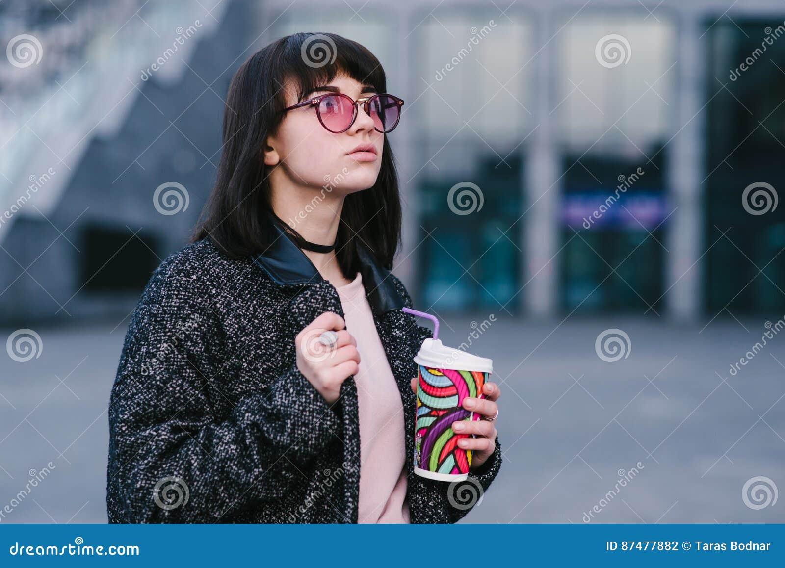 Стильная и красивая усмехаясь девушка в розовых стеклах битника держа чашку кофе и прогулку вокруг города