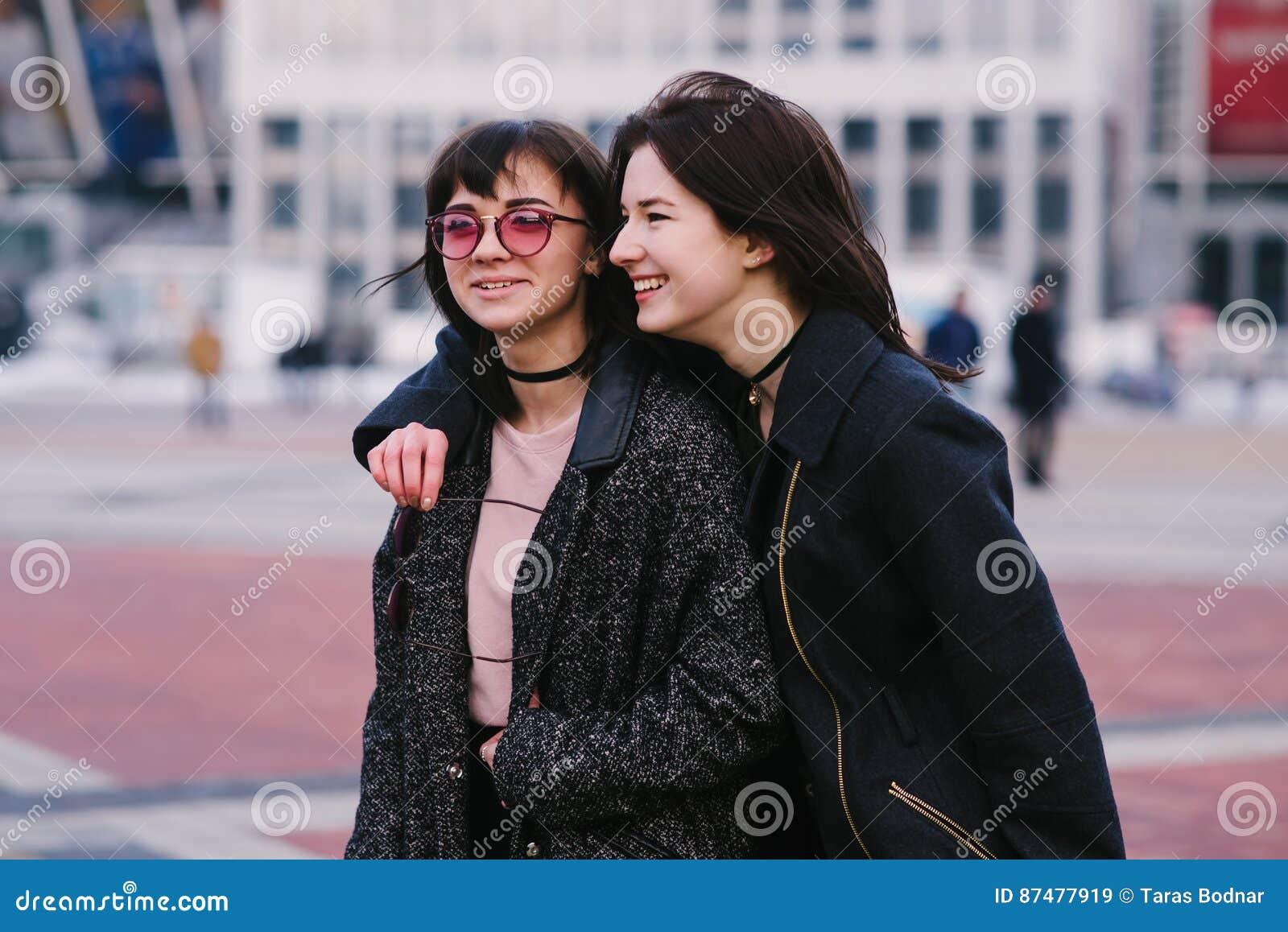 2 стильное и красивые друзья маленьких девочек нося вскользь прогулку вокруг города и улыбки
