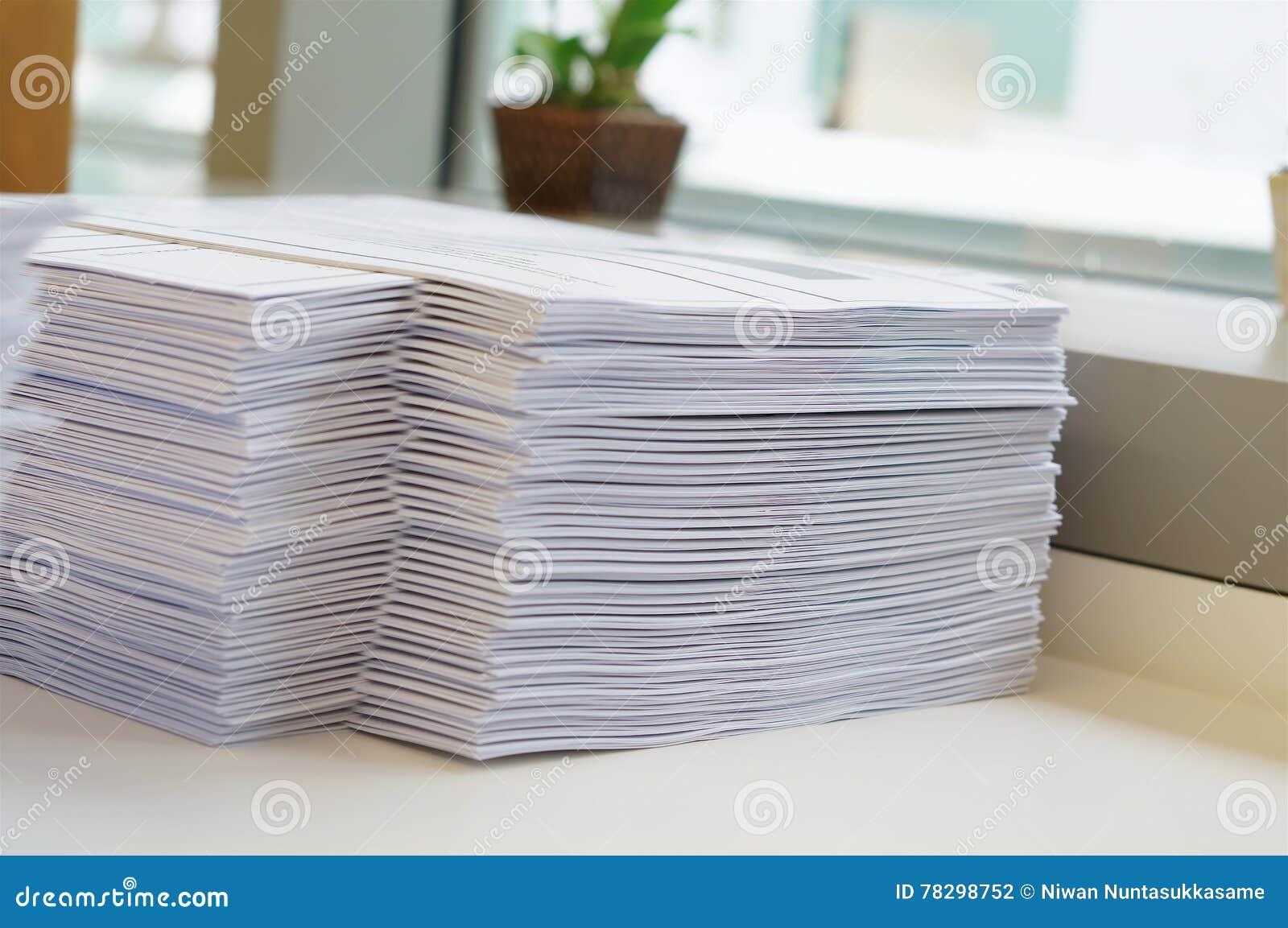 Стог рабочего листа бумаг около окна