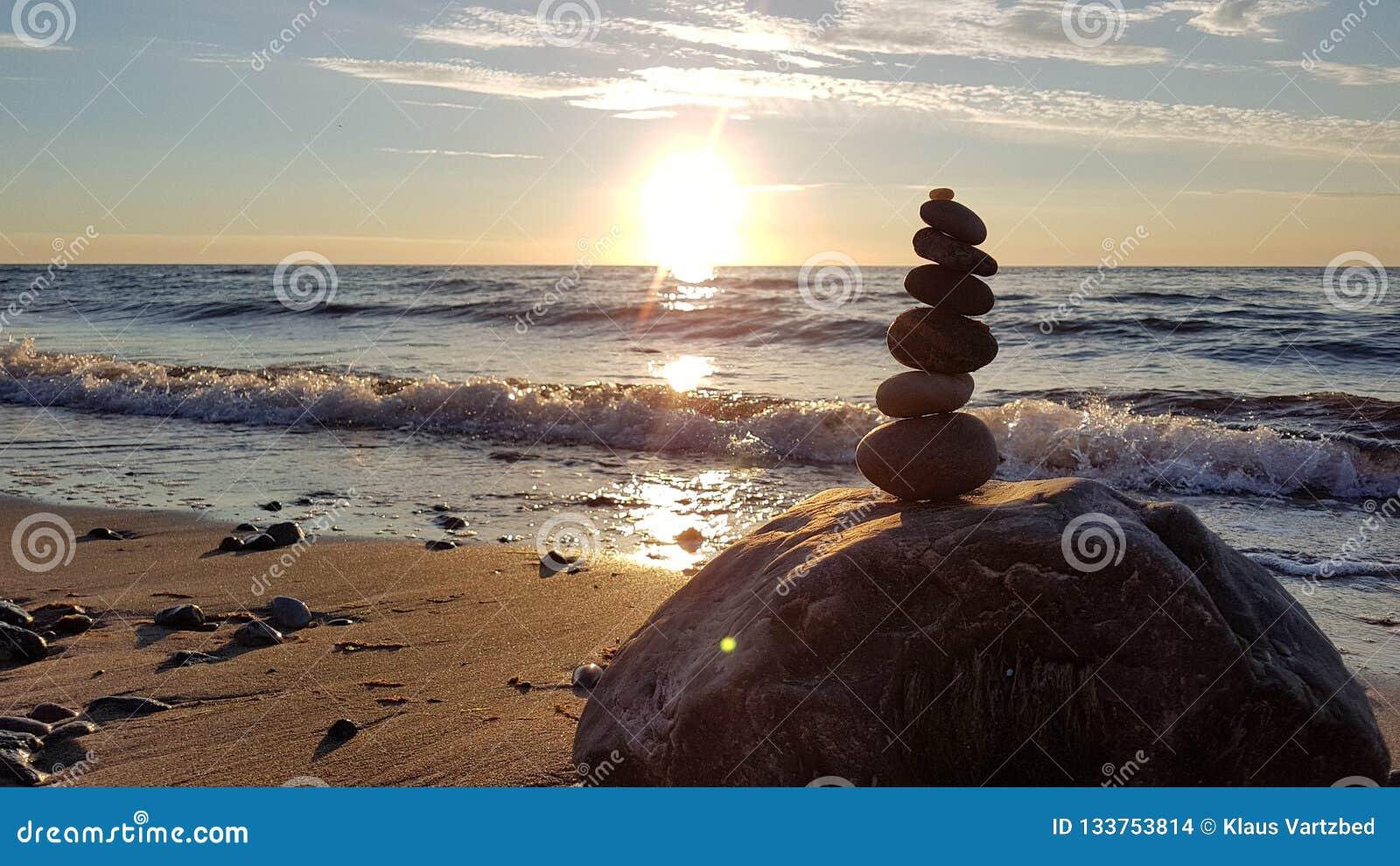 Стог различных камней в балансе на заходе солнца пляжа
