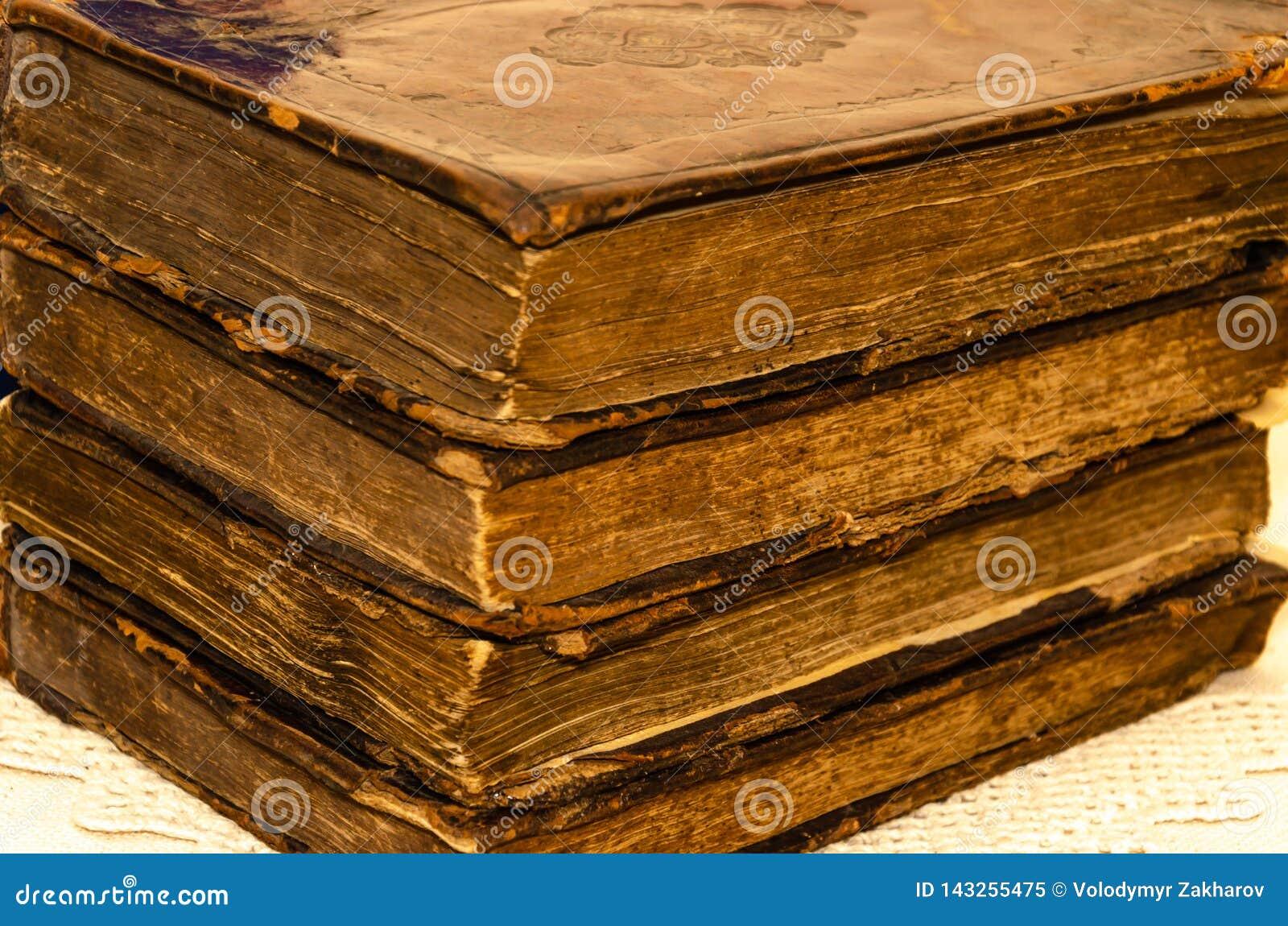 Стог старых и несенных кожаных книг крышки с выбивать листового золота