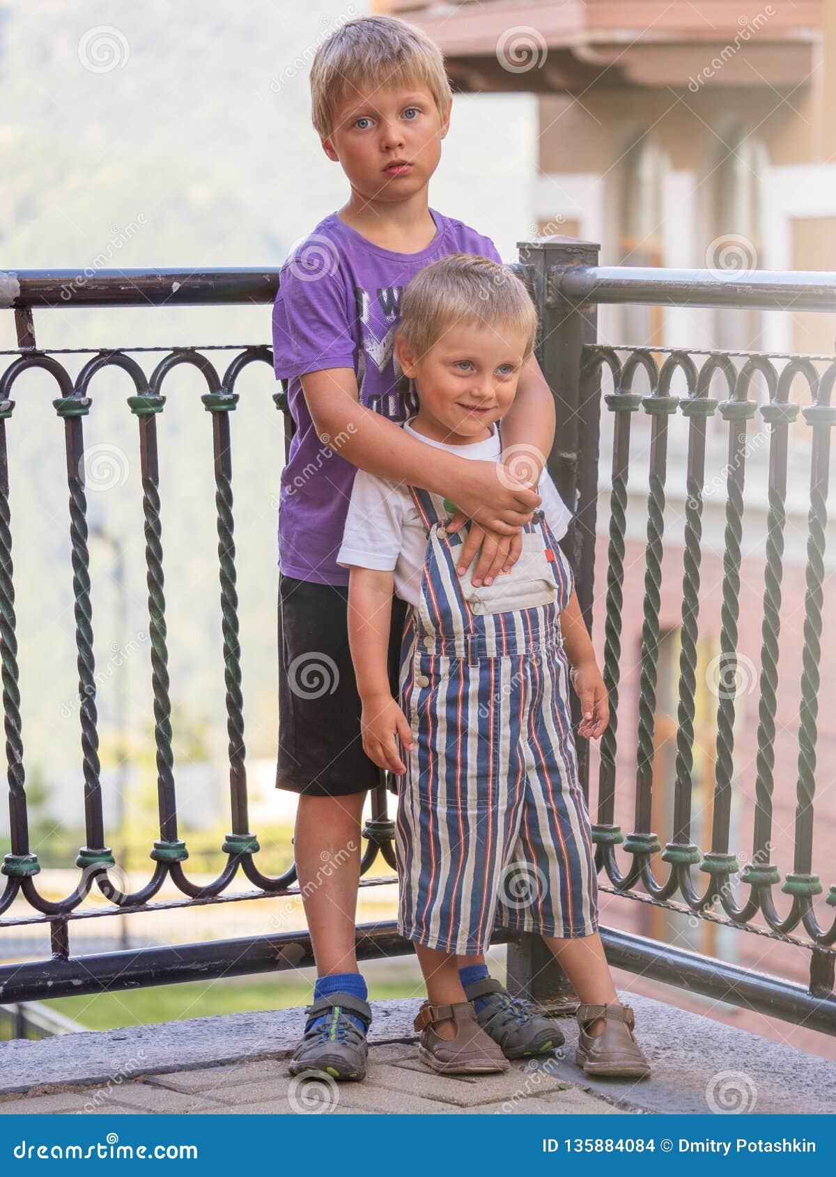 Стойка 2 мальчиков обнимая на заходе солнца