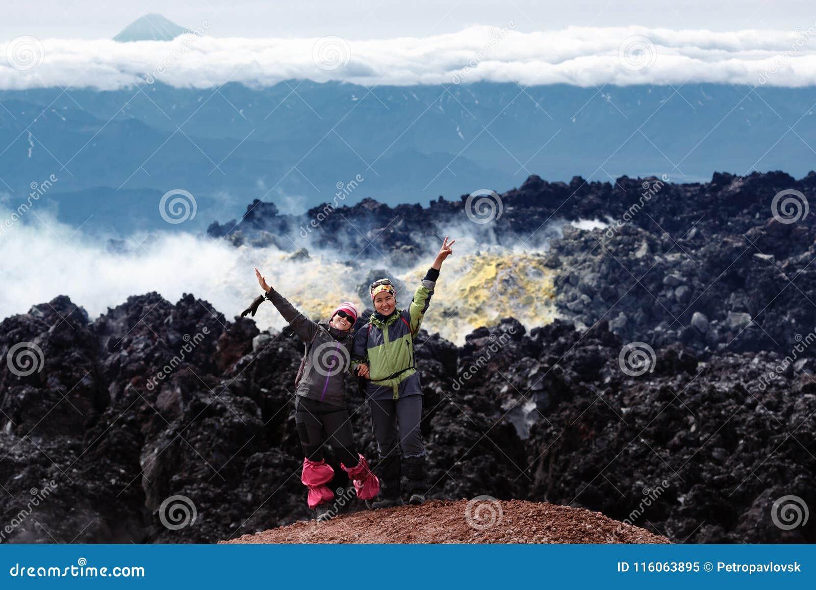 Стойка 2 радостная подруг в кратере действующего вулкана