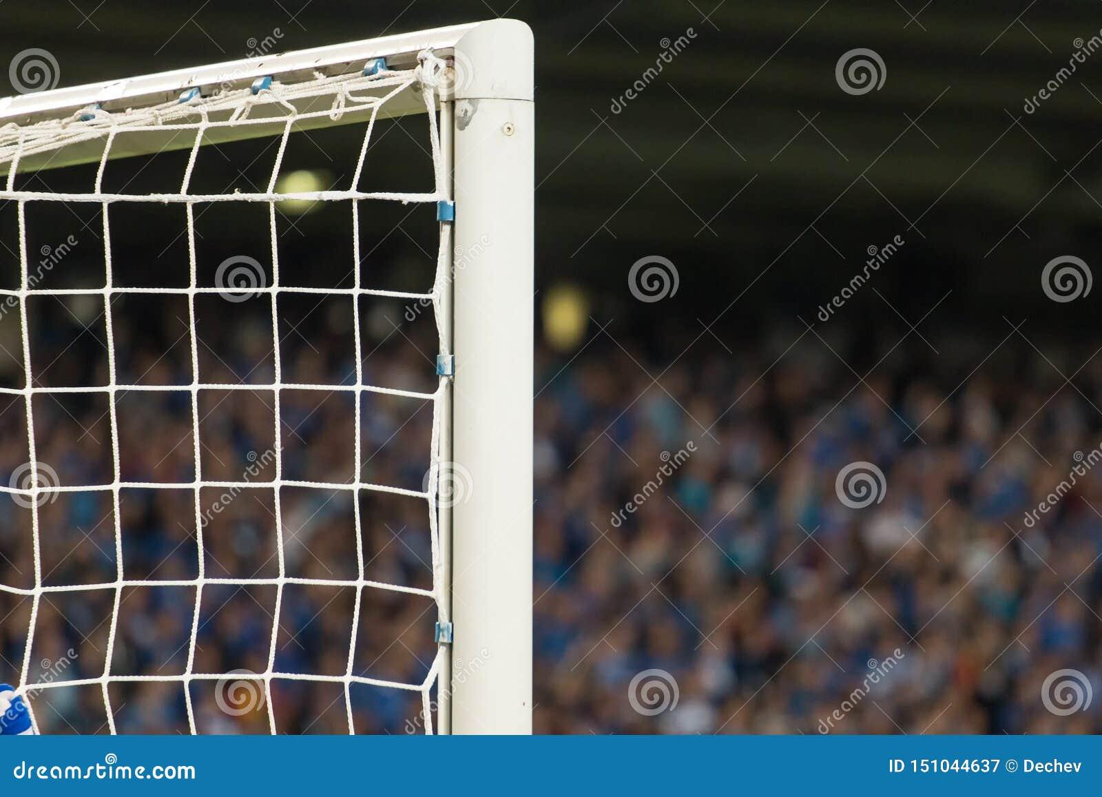 Столб цели с поклонниками футбола на заднем плане