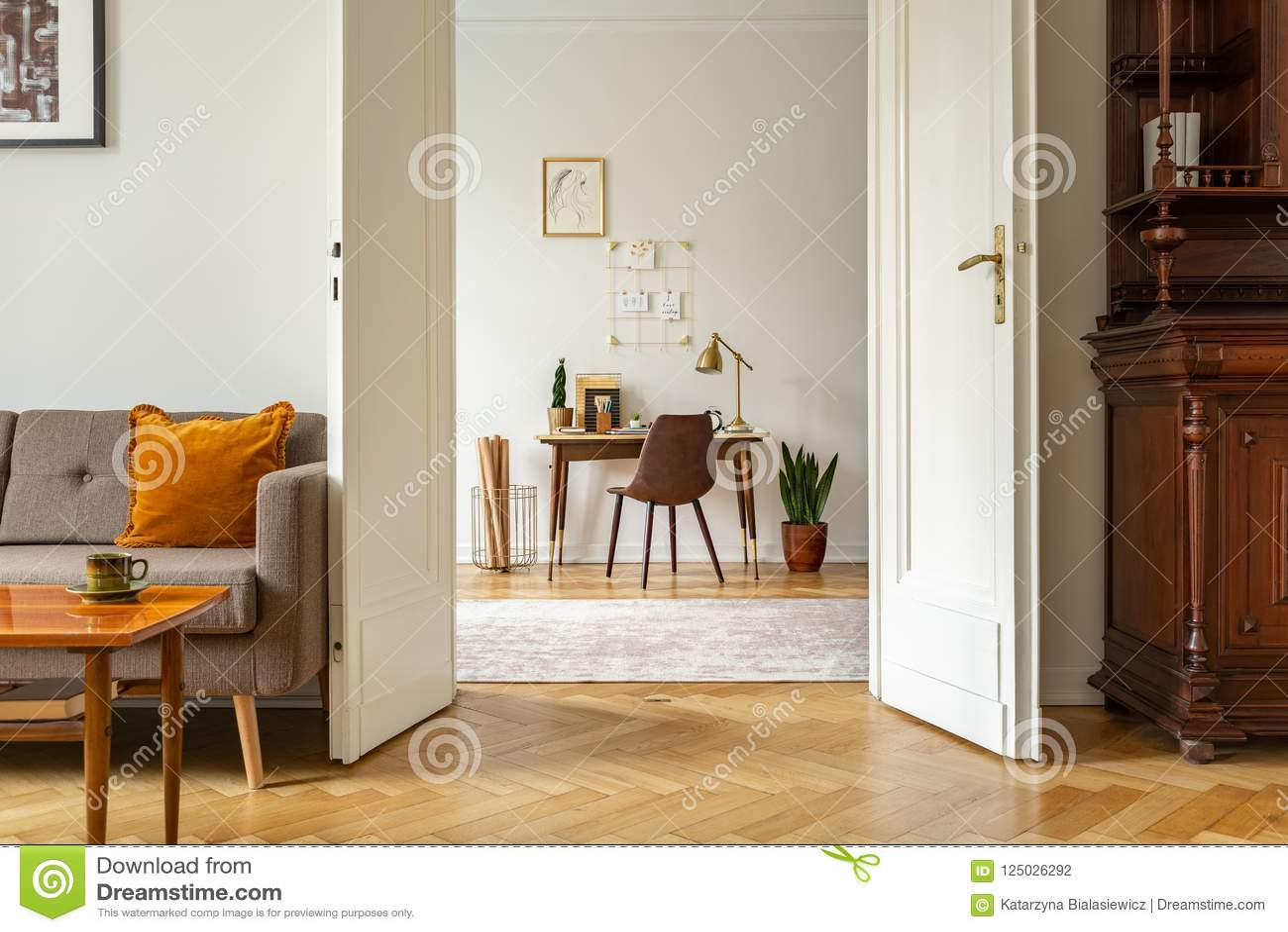 Стол и стул в интерьере домашнего офиса Взгляд через дверь винтажной живущей комнаты Реальное фото