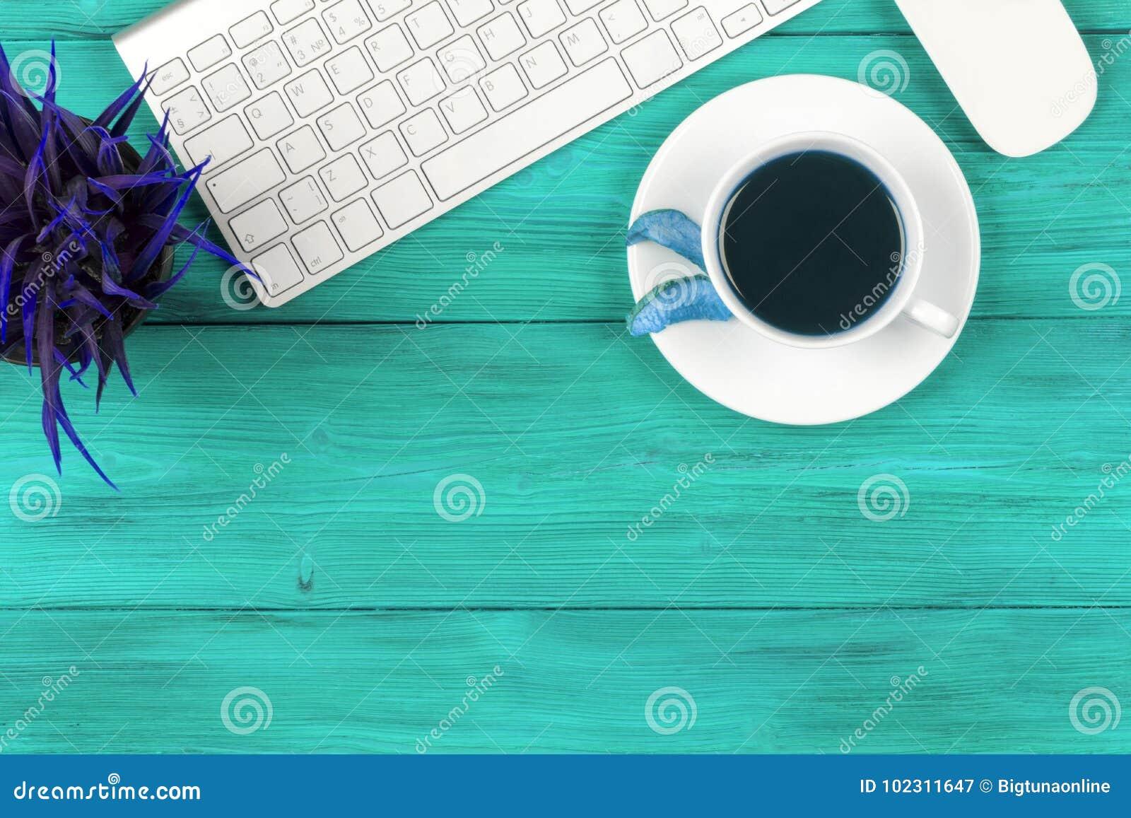 Стол офиса с космосом экземпляра Приборы беспроводная клавиатура и мышь цифров на голубом деревянном столе с чашкой свежего кофе,