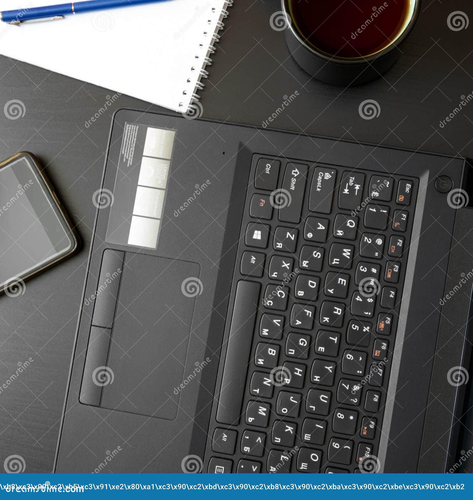 Стол с ноутбуком, умным телефоном, тетрадями, ручками, eyeglasses и чашкой чаю Взгляд бортового угла