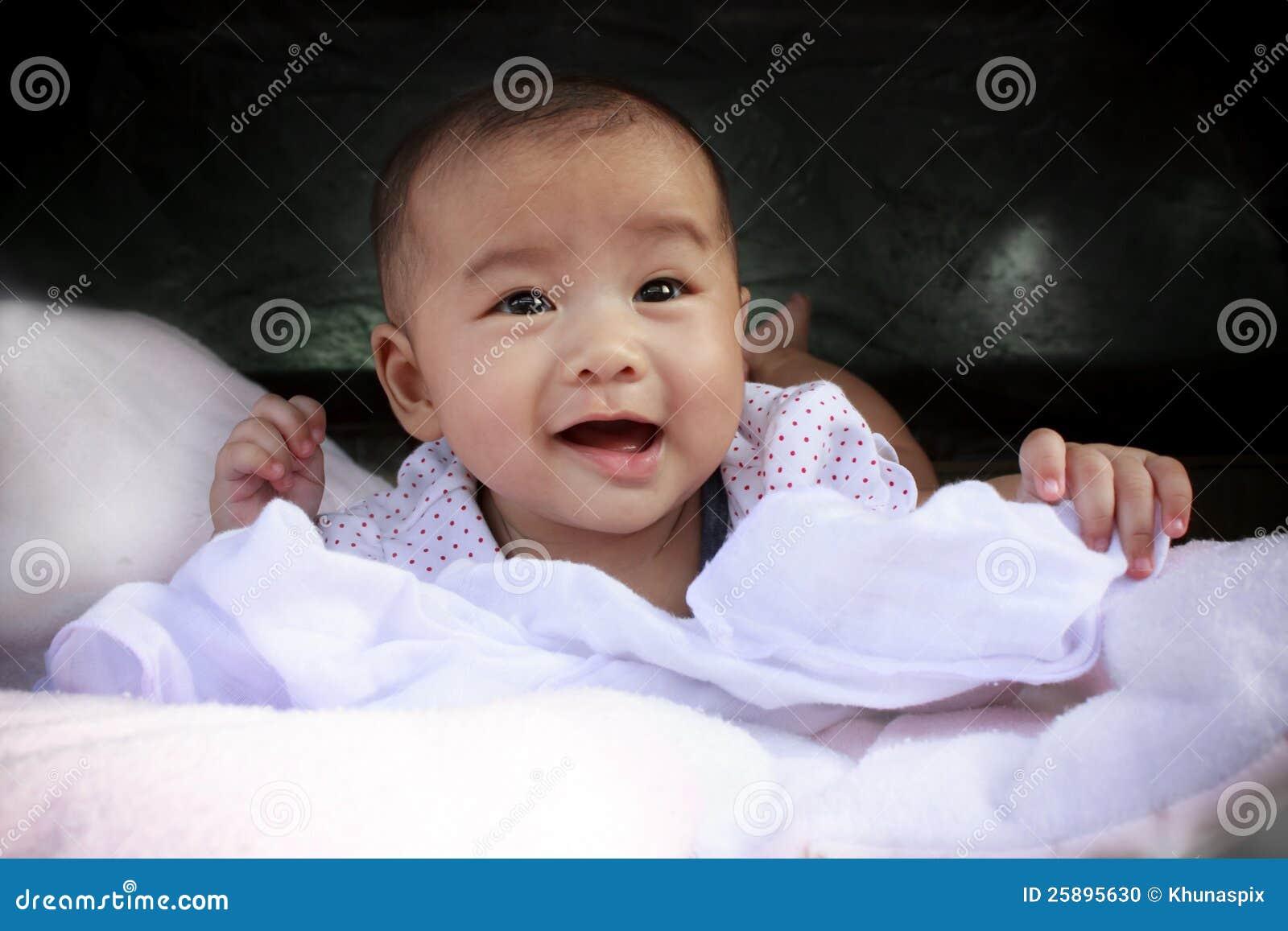 Сторона милого азиатского младенца ся лежала на кровати