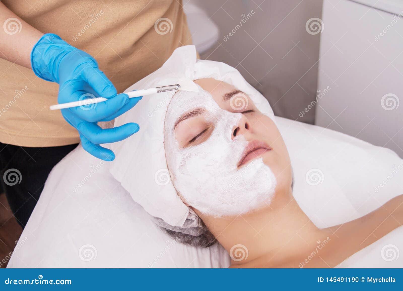 Сторона слезая маску, косметическую процедуру спа, skincare Женщина получая лицевую заботу beautician на салоне спа