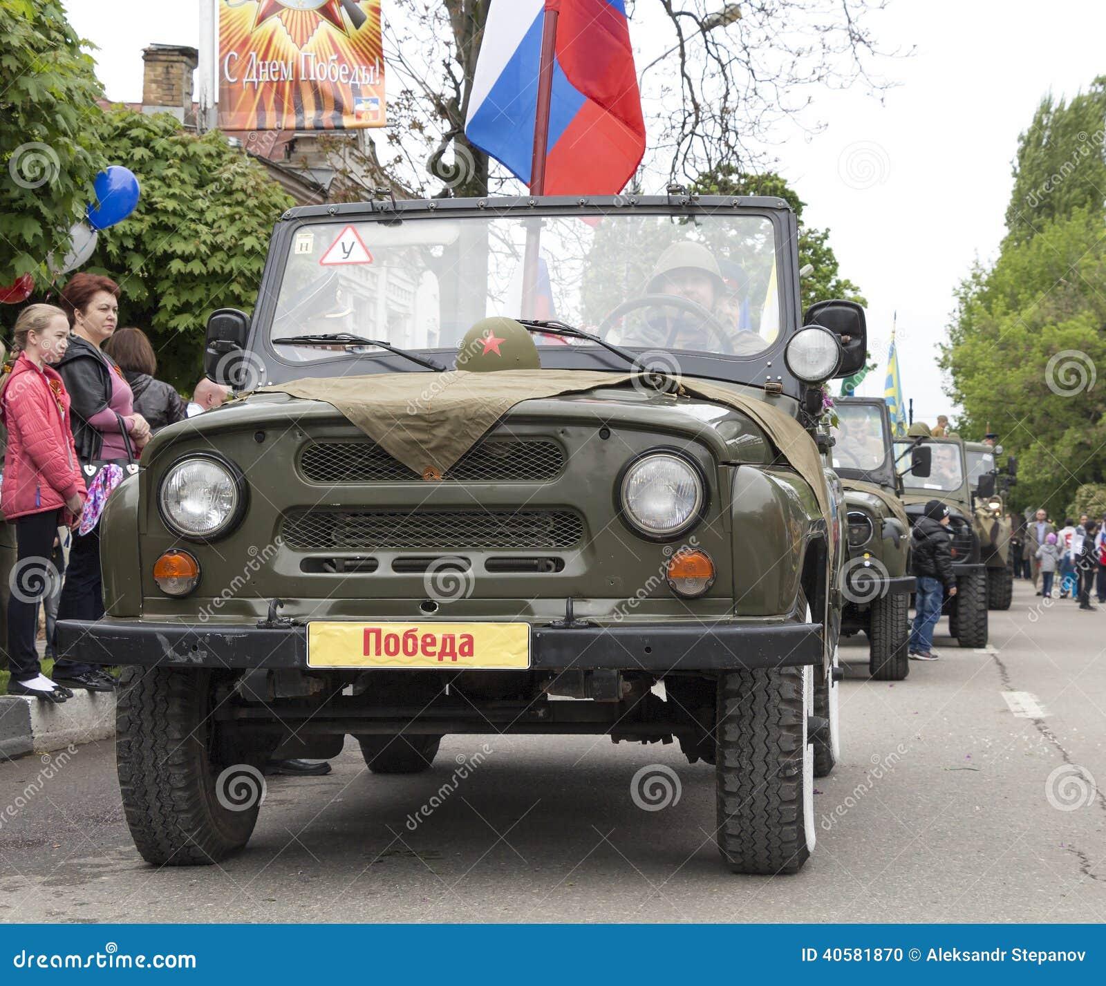 Столбец воинских автомобилей с ветеранами бортовыми на параде в почетности