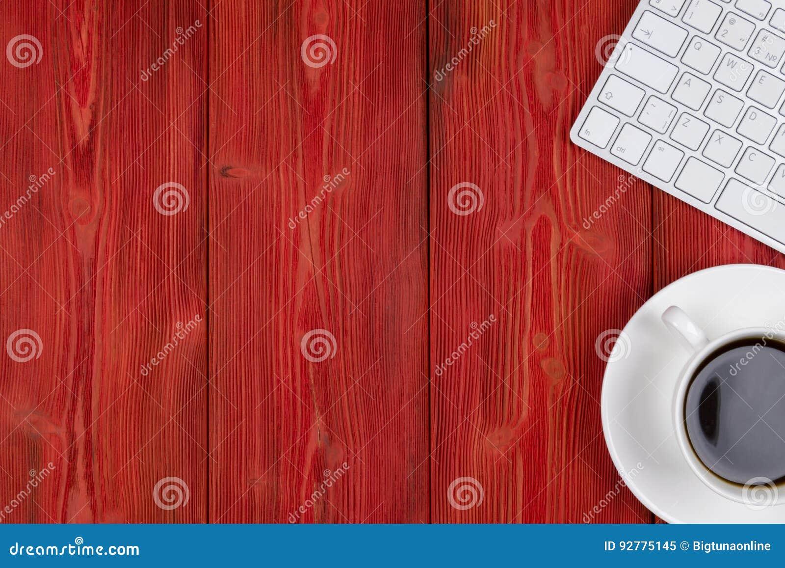 Стол офиса с космосом экземпляра Приборы беспроводная клавиатура и мышь цифров на красном деревянном столе с чашкой кофе, взгляд