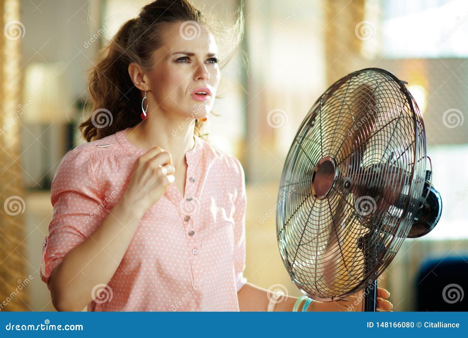 Страдание женщины от жары лета пока стоящ перед вентилятором