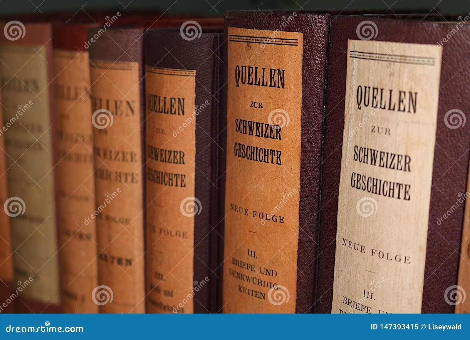 Строка античных книг с кожаными крышками и немецкими названиями в черных буквах