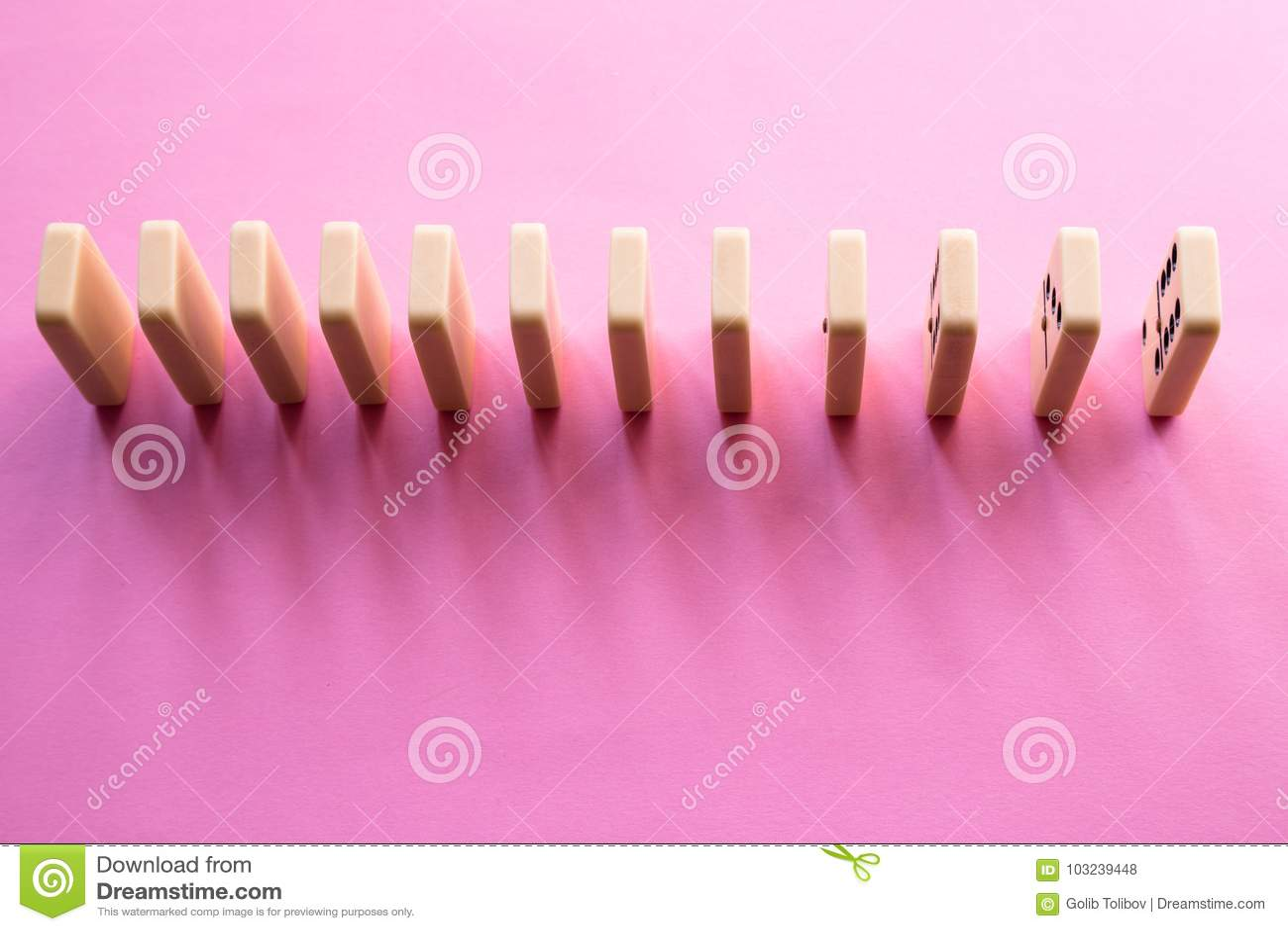 Строка домино на розовой предпосылке Плоское положение