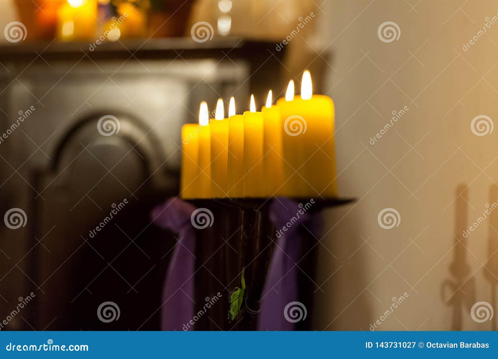 Строка желтых свечей в церков