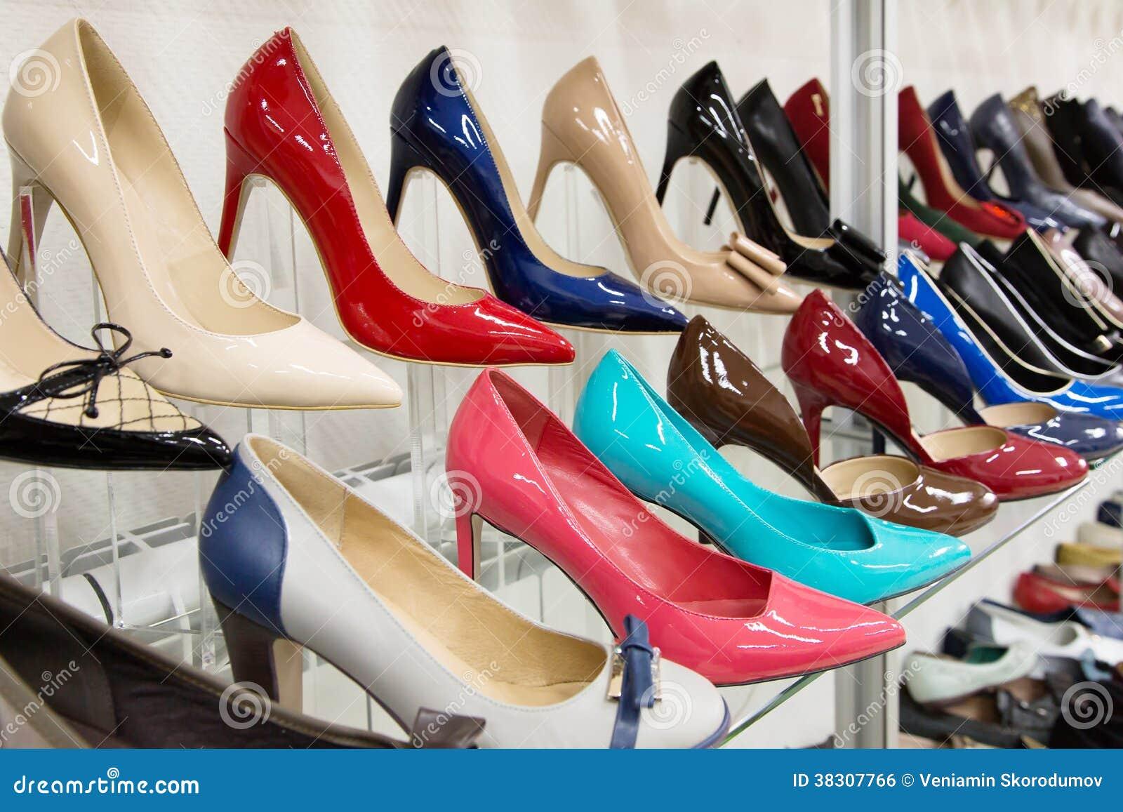 Строки ботинок красивых женщин на витринах магазина
