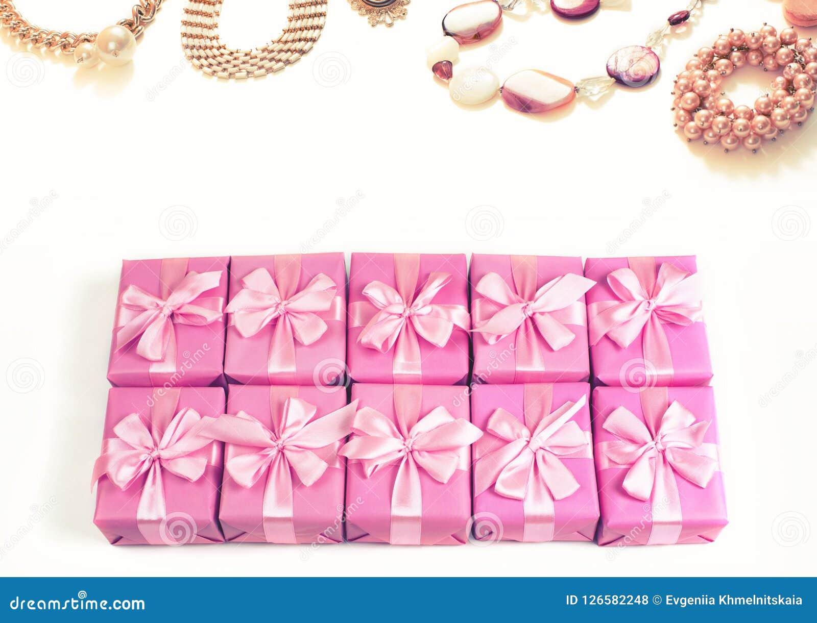Строки коробок с сатинировкой орденской ленты подарков обхватывают розовые аксессуары моды для взгляд сверху браслета a ожерелья