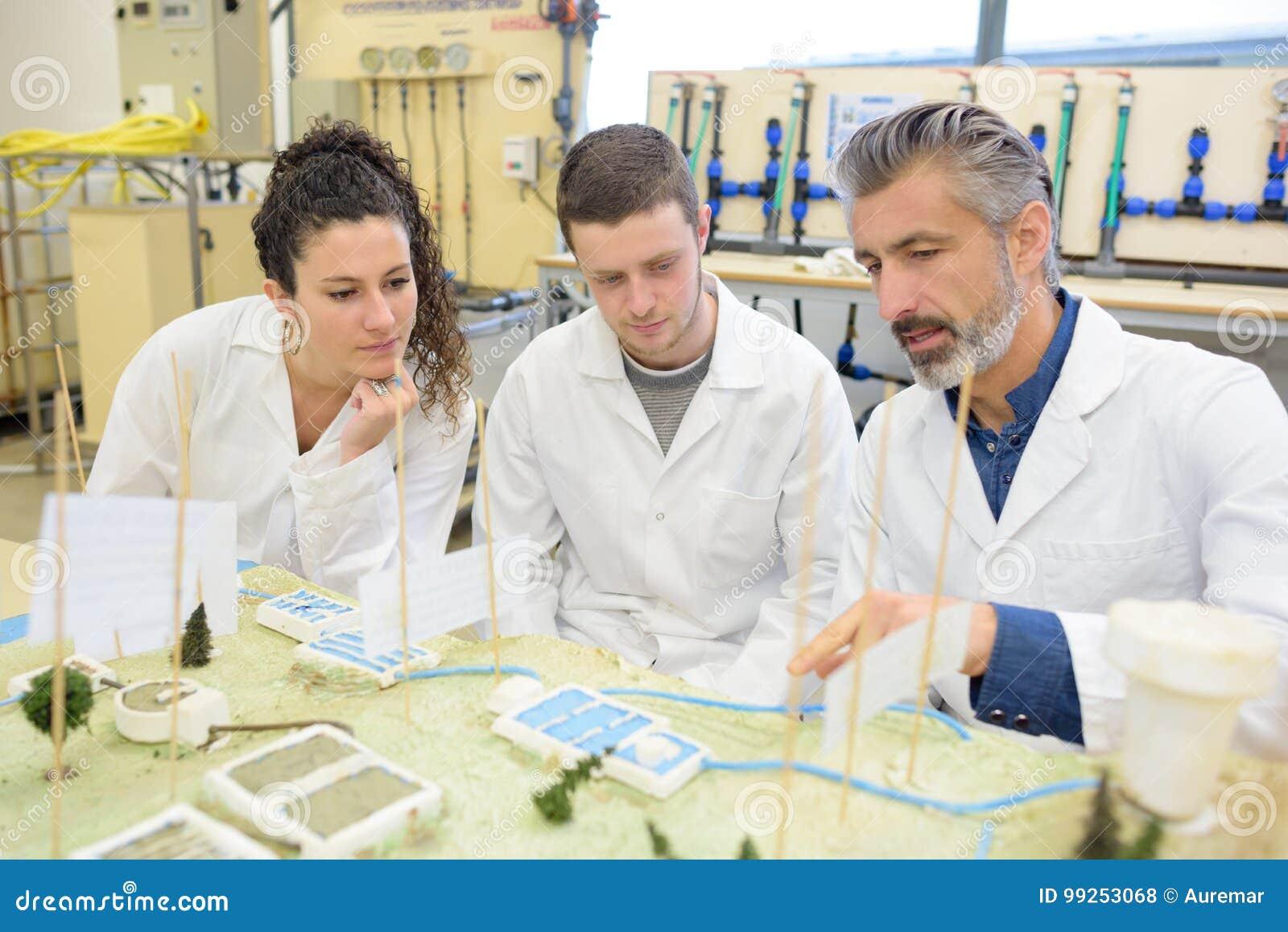 2 студента работая в классе с их учителем