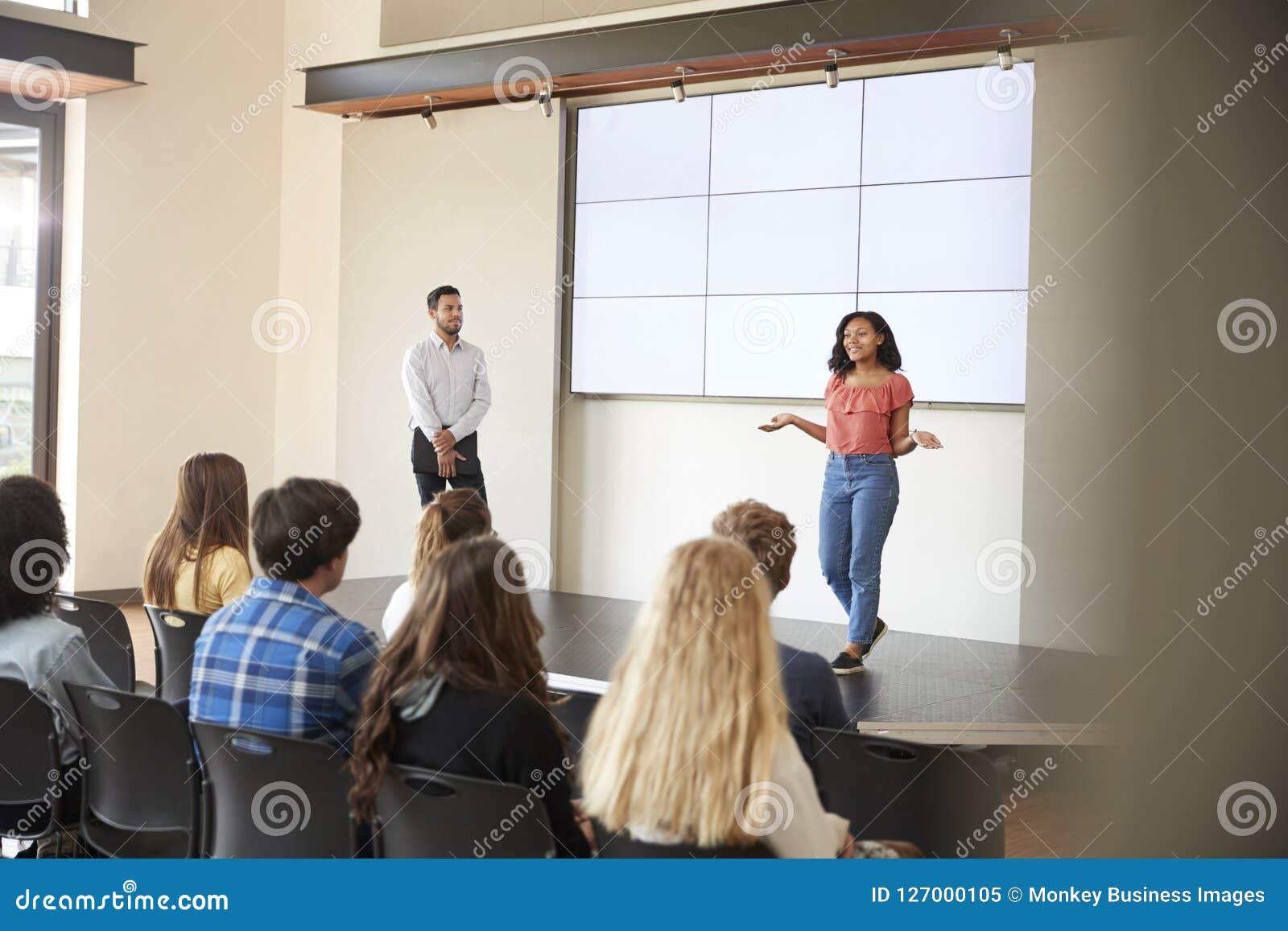 Студентка давая представление к классу средней школы перед экраном