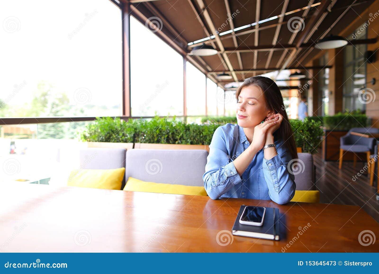 Студентка сидя на кафе со смартфоном и тетради на таблице