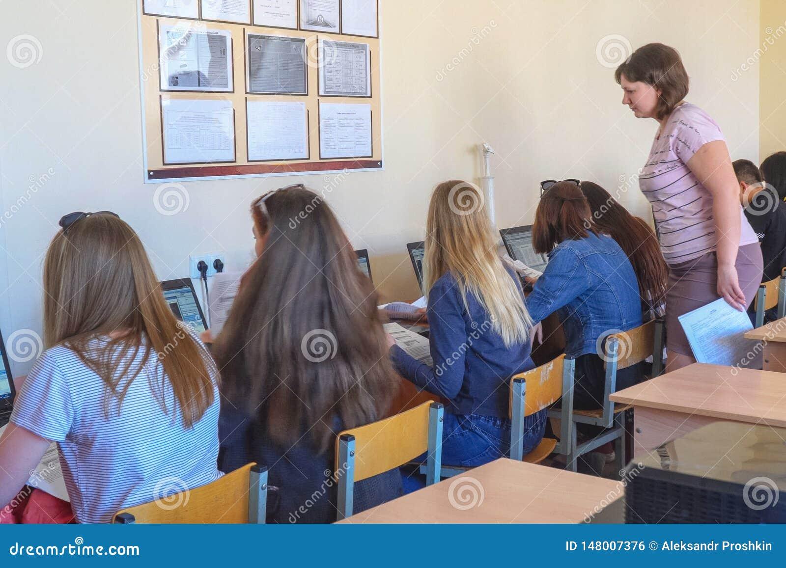 Студенты девушек в классе компьютера с учителем