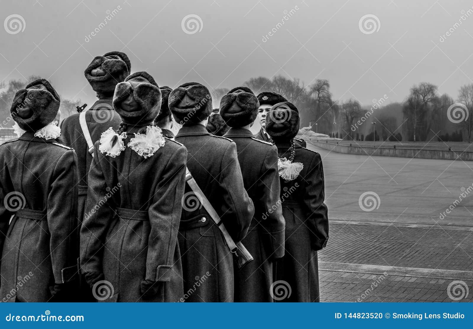 Студенты и солдаты маршируя и оплачивая дань