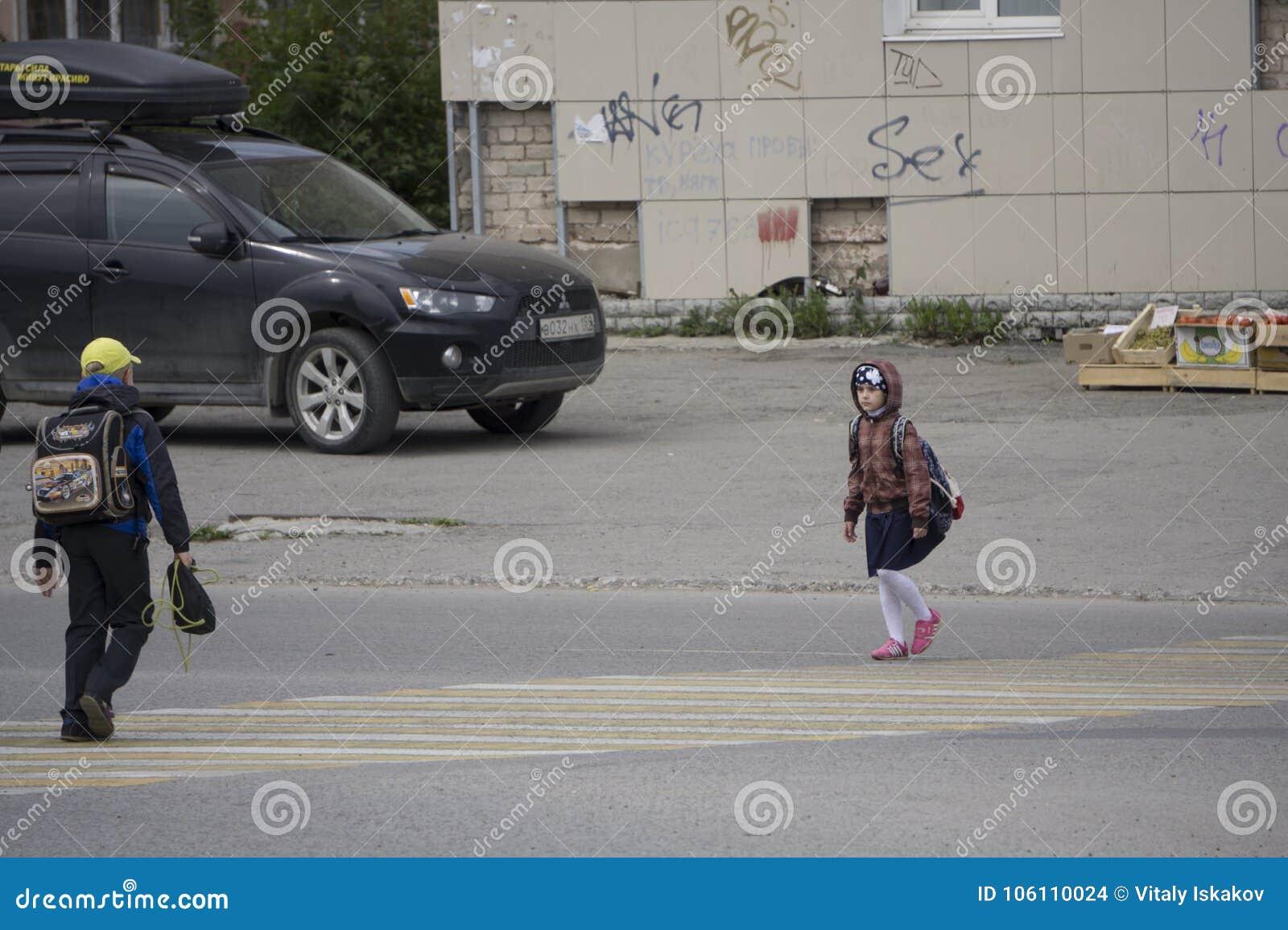 Студенты пересекая зебру на улице в Berezniki, России, 4-ого сентября