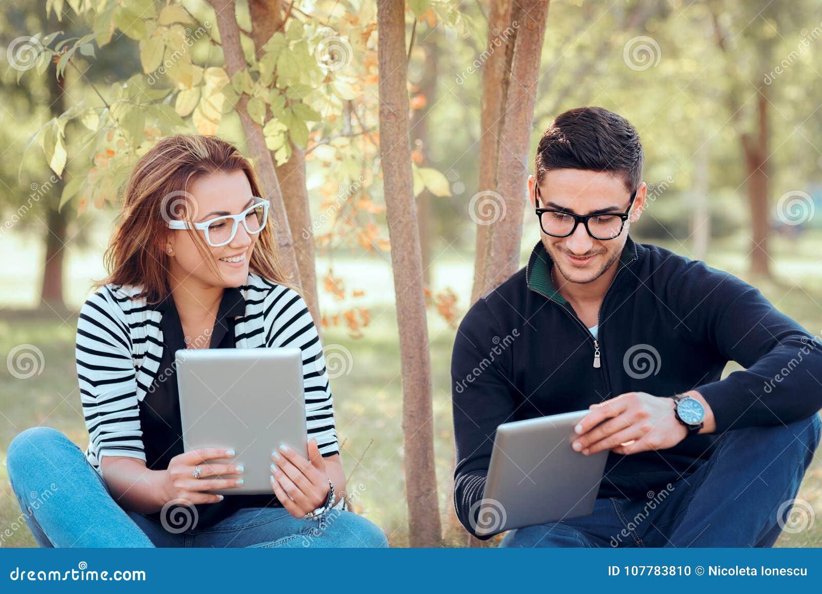 Студенты при таблетки цифров сидя на траве в университетском кампусе