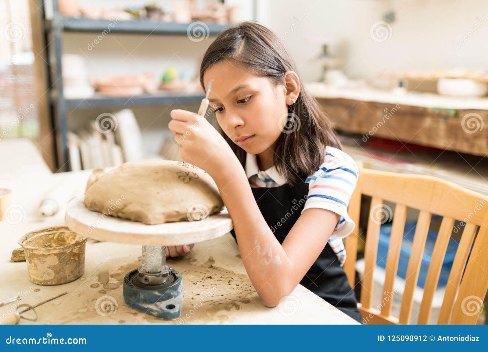 Студент высекая цветочный узор на глине во время класса гончарни