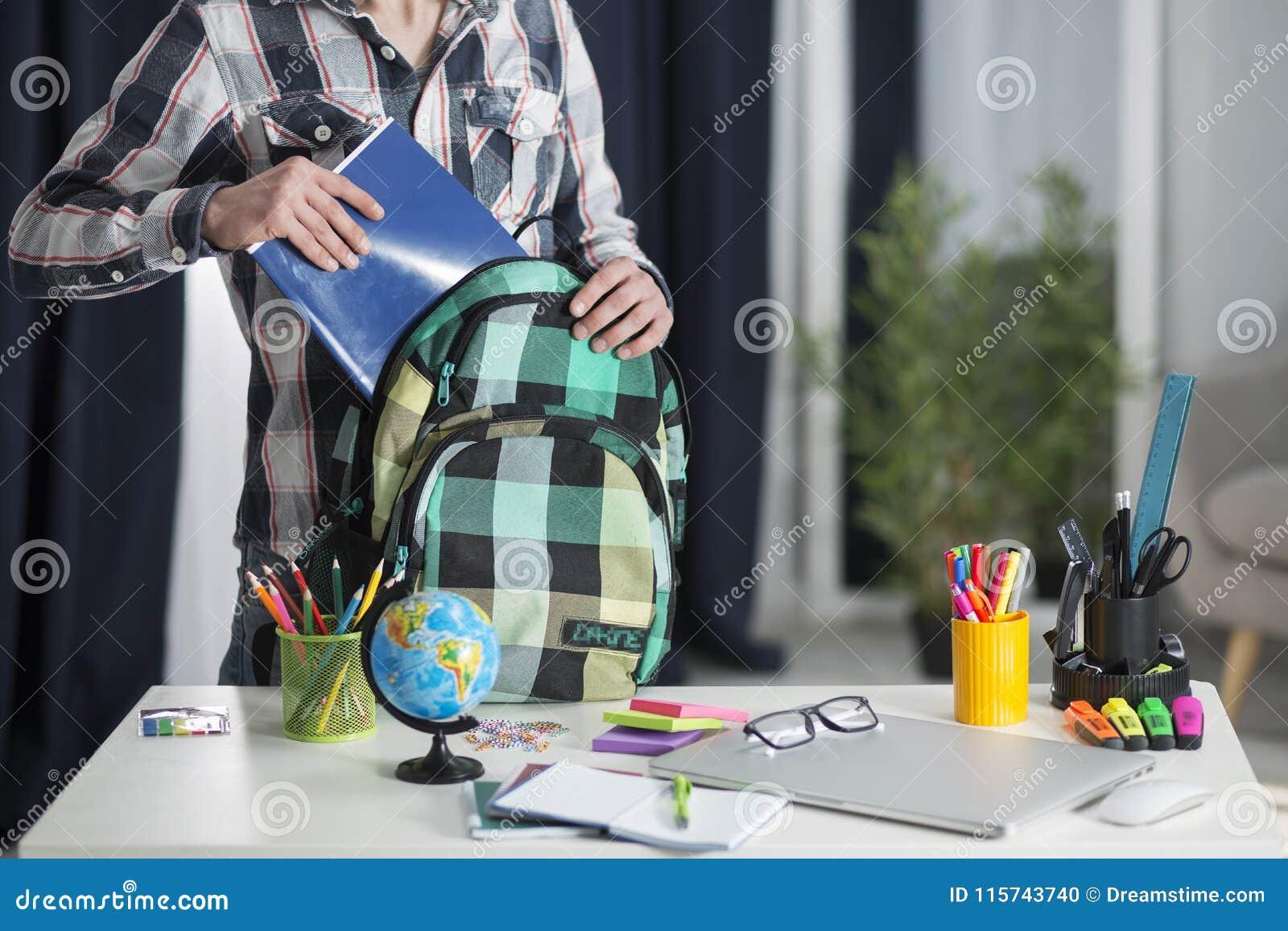 Студент принимает тетрадь от его рюкзака