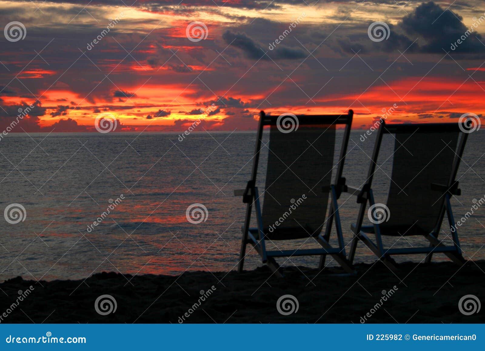 стулы пляжа смотря вне заход солнца