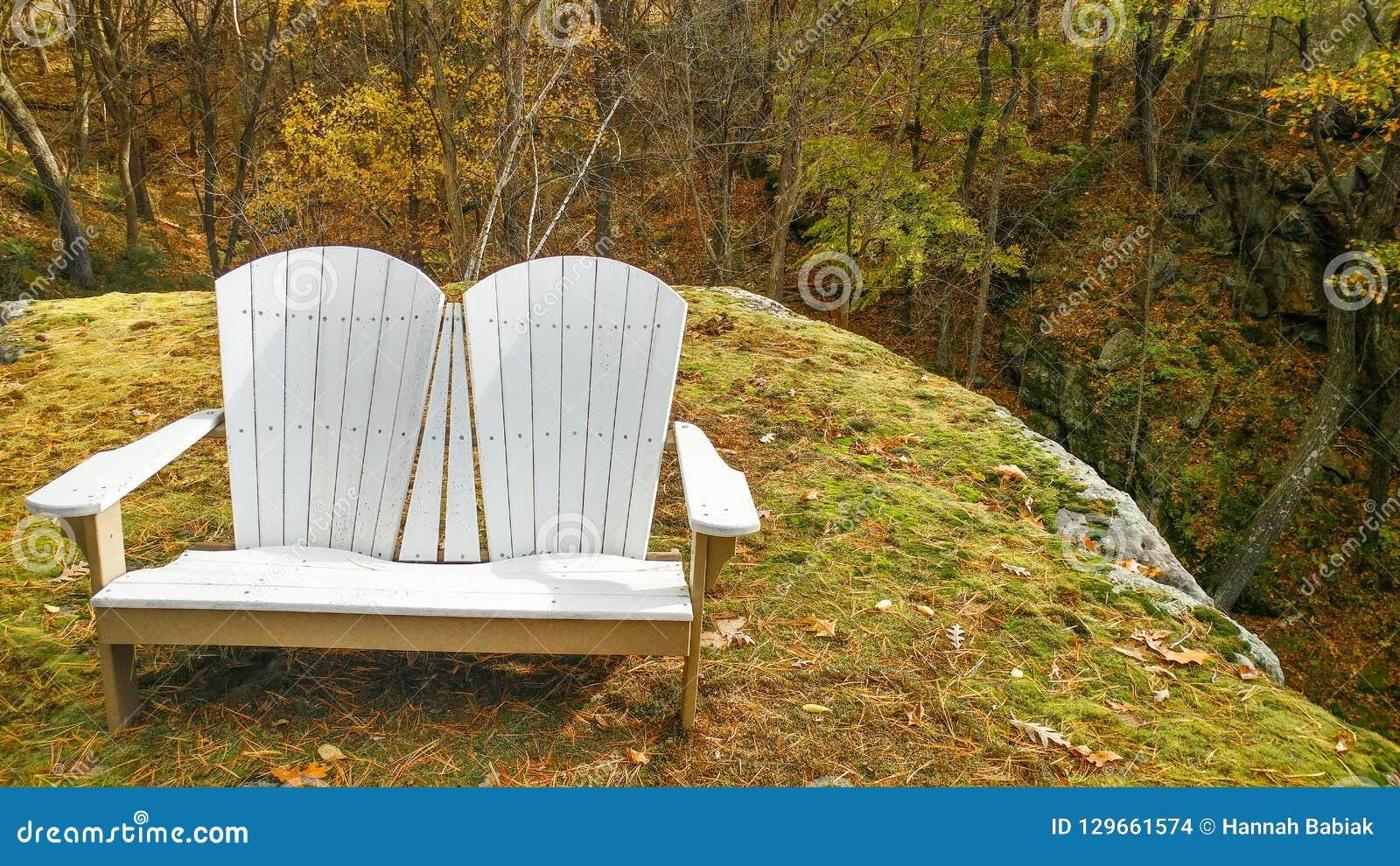 Стул места любов Adirondack на уступе утеса