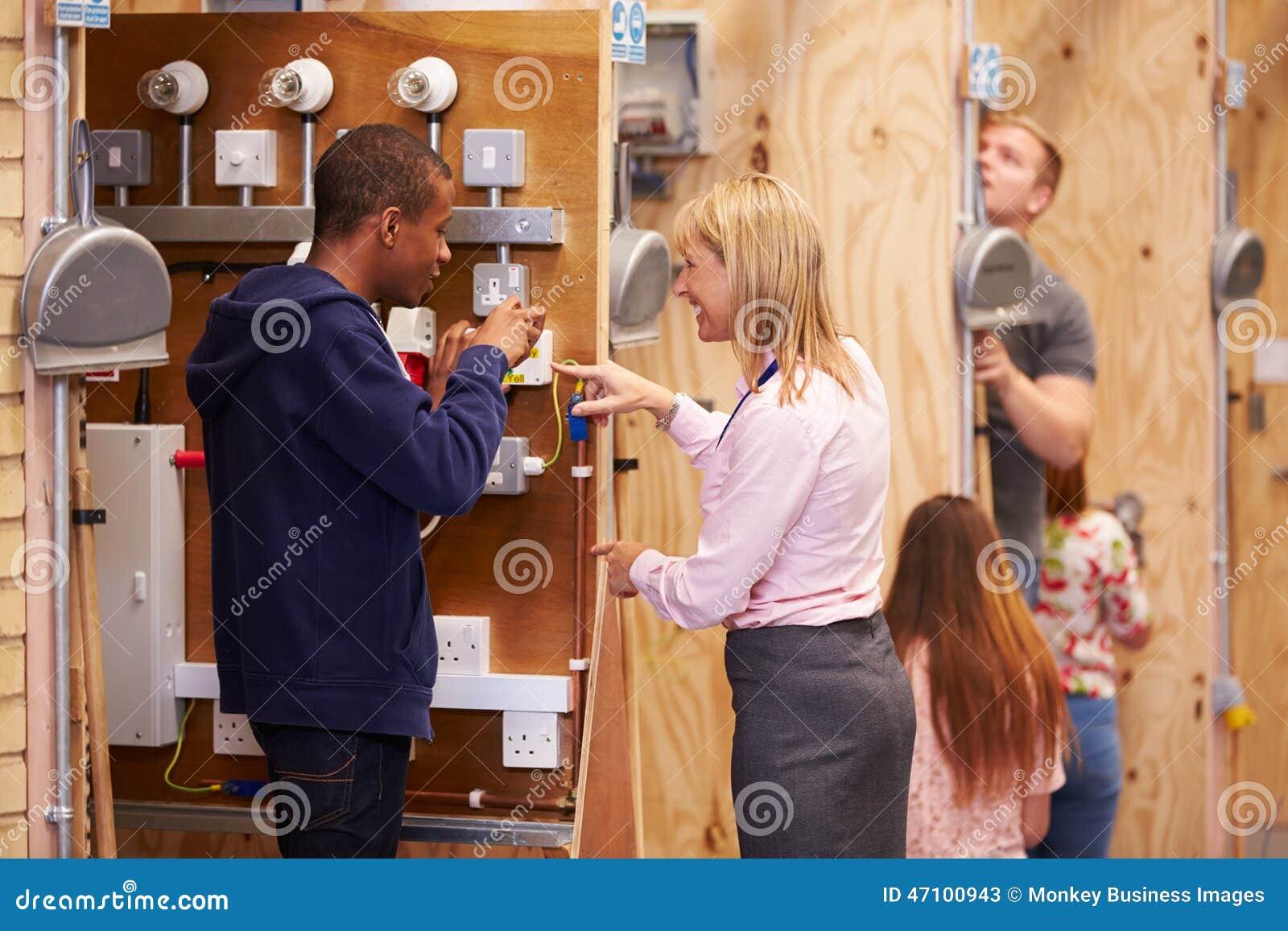Студенты порции учительницы тренируя для того чтобы быть электриками