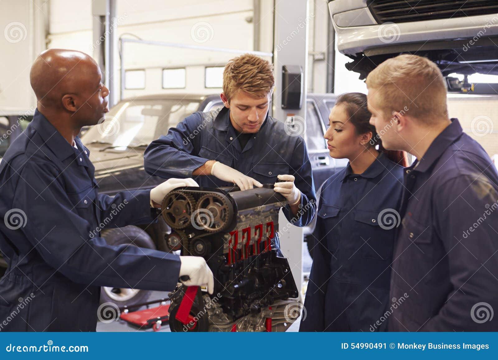 Студенты порции учителя тренируя для того чтобы быть механиками автомобиля