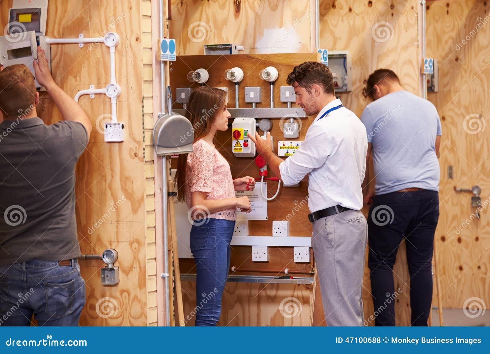 Студенты порции учителя тренируя для того чтобы быть электриками