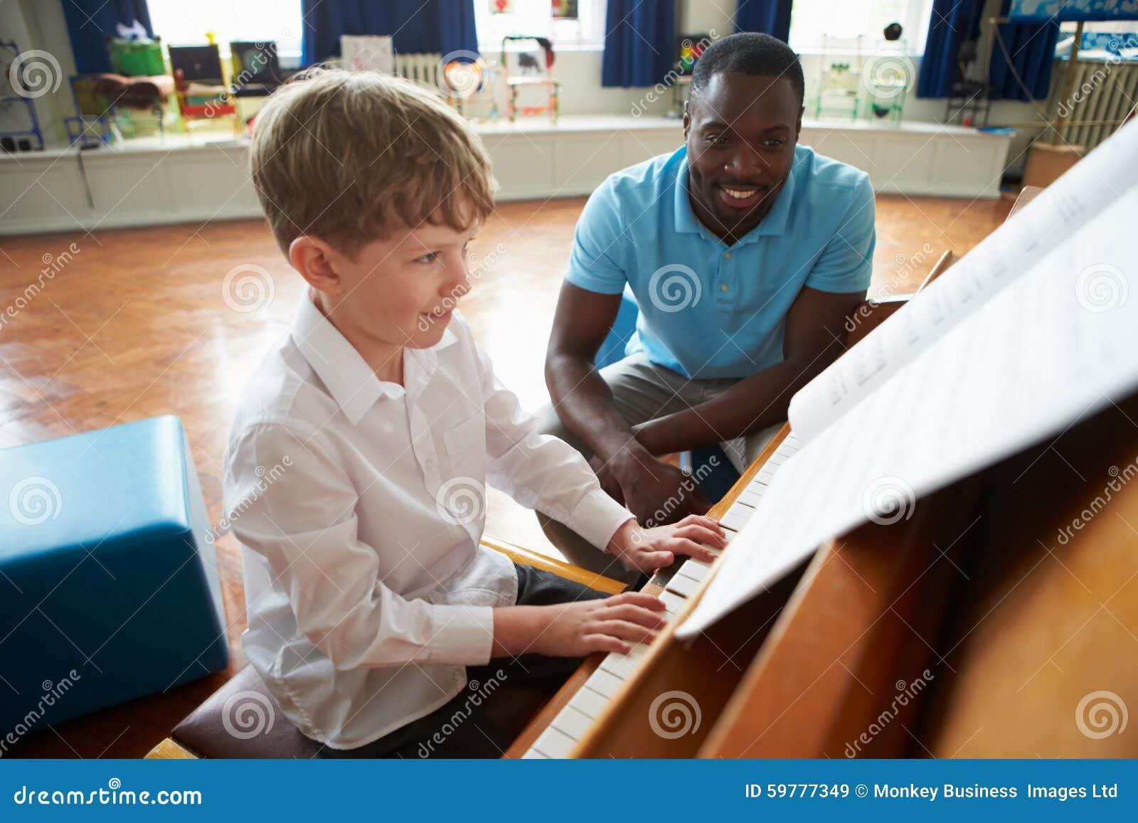 Студент наслаждаясь уроком рояля с учителем