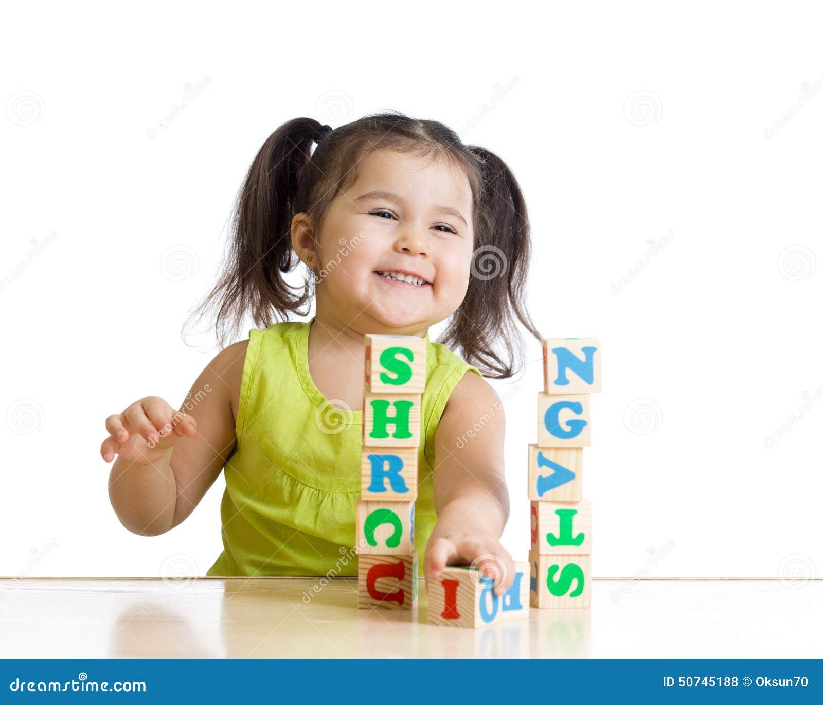 Студент начальной школы играя блоки письма