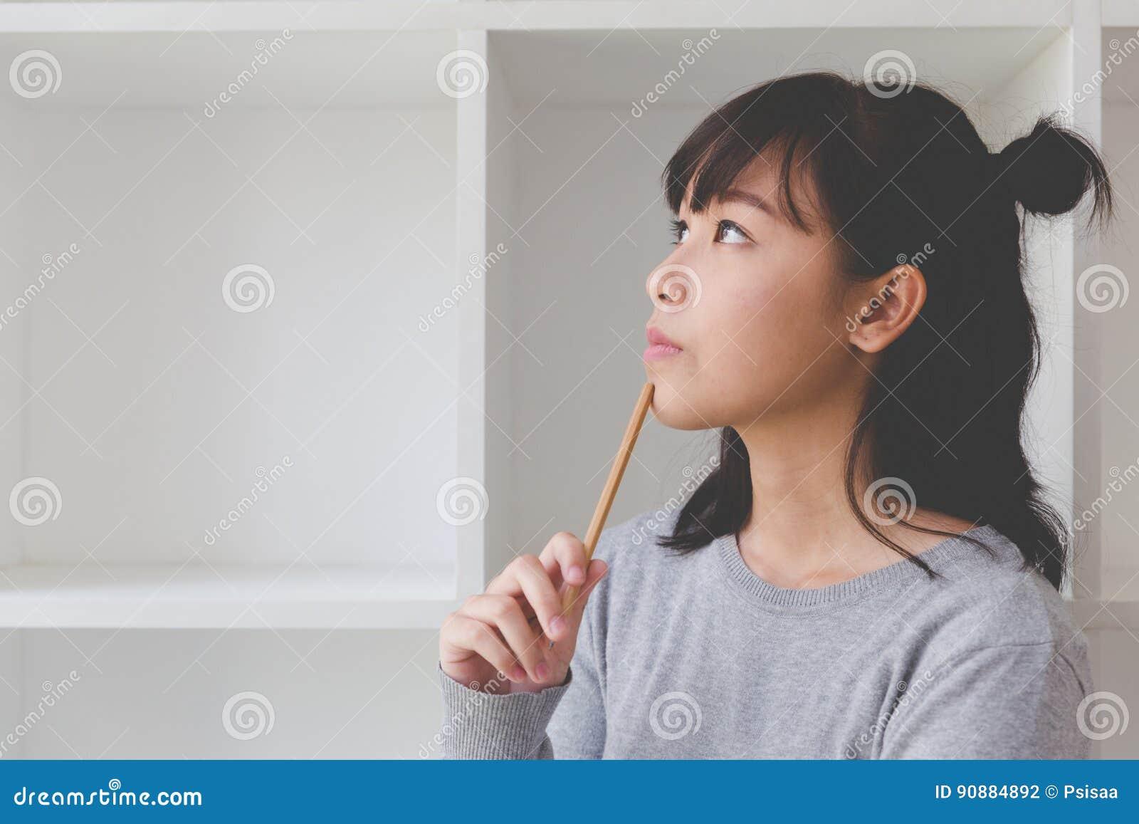 студент подростка азиатской девушки женский думая что-то около шиканья