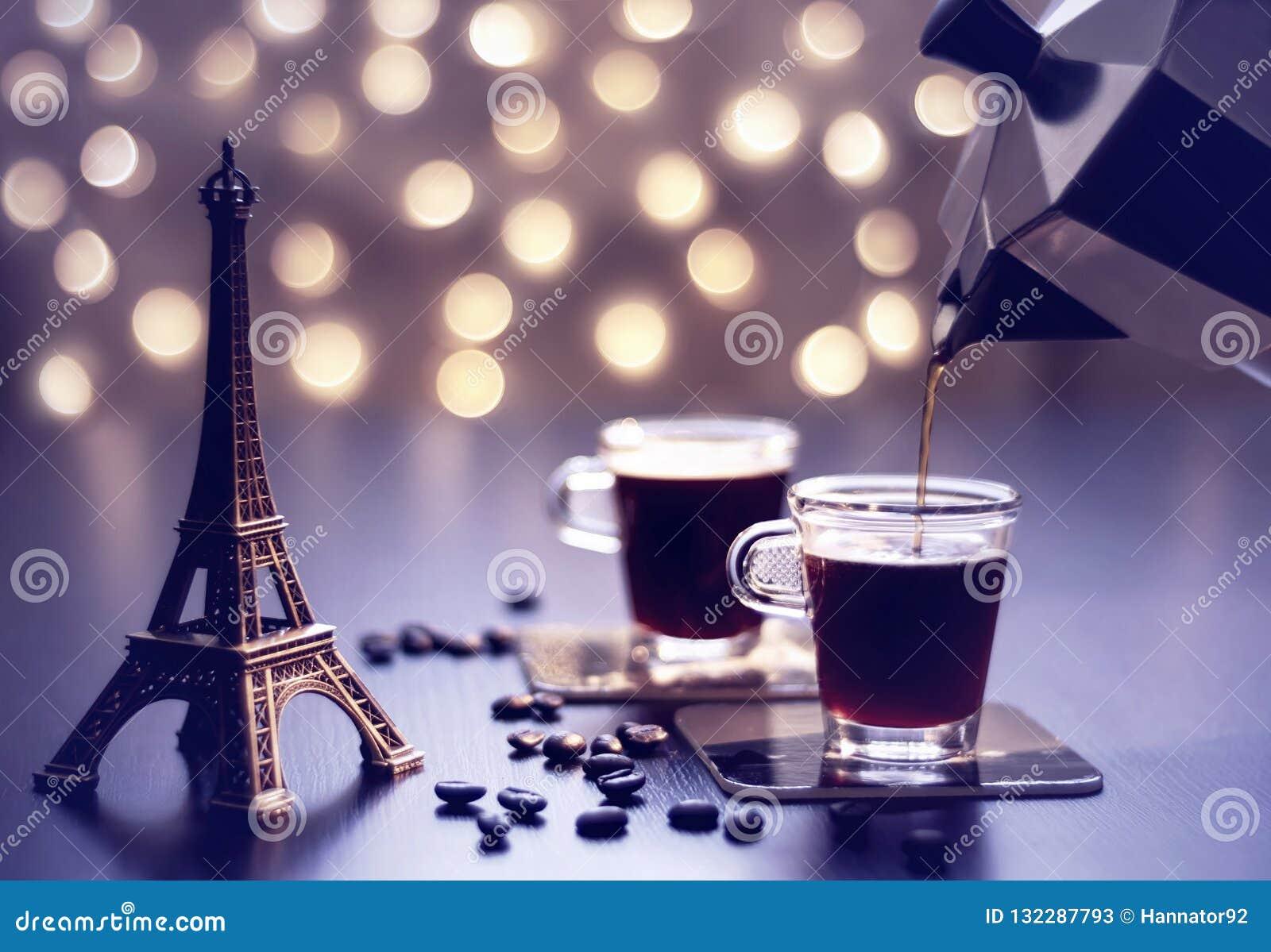 Сувенир Эйфелевой башни witn чашек кофе на таблице и красивом bokeh золота